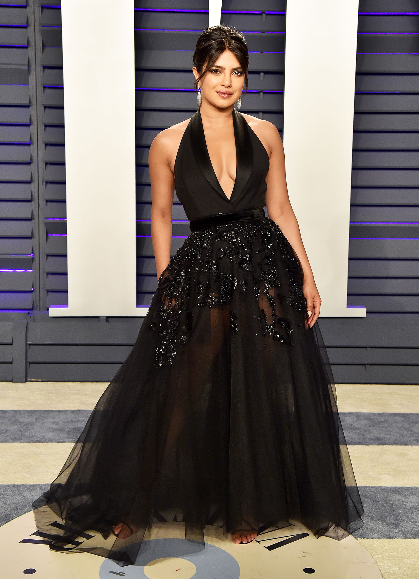 Priyanka Chopra vanity fair 2019 black gown - She proved black is anything but boring in a plunging black Elie Saab ball gown at the 2019 Vanity Fair Oscar Party.