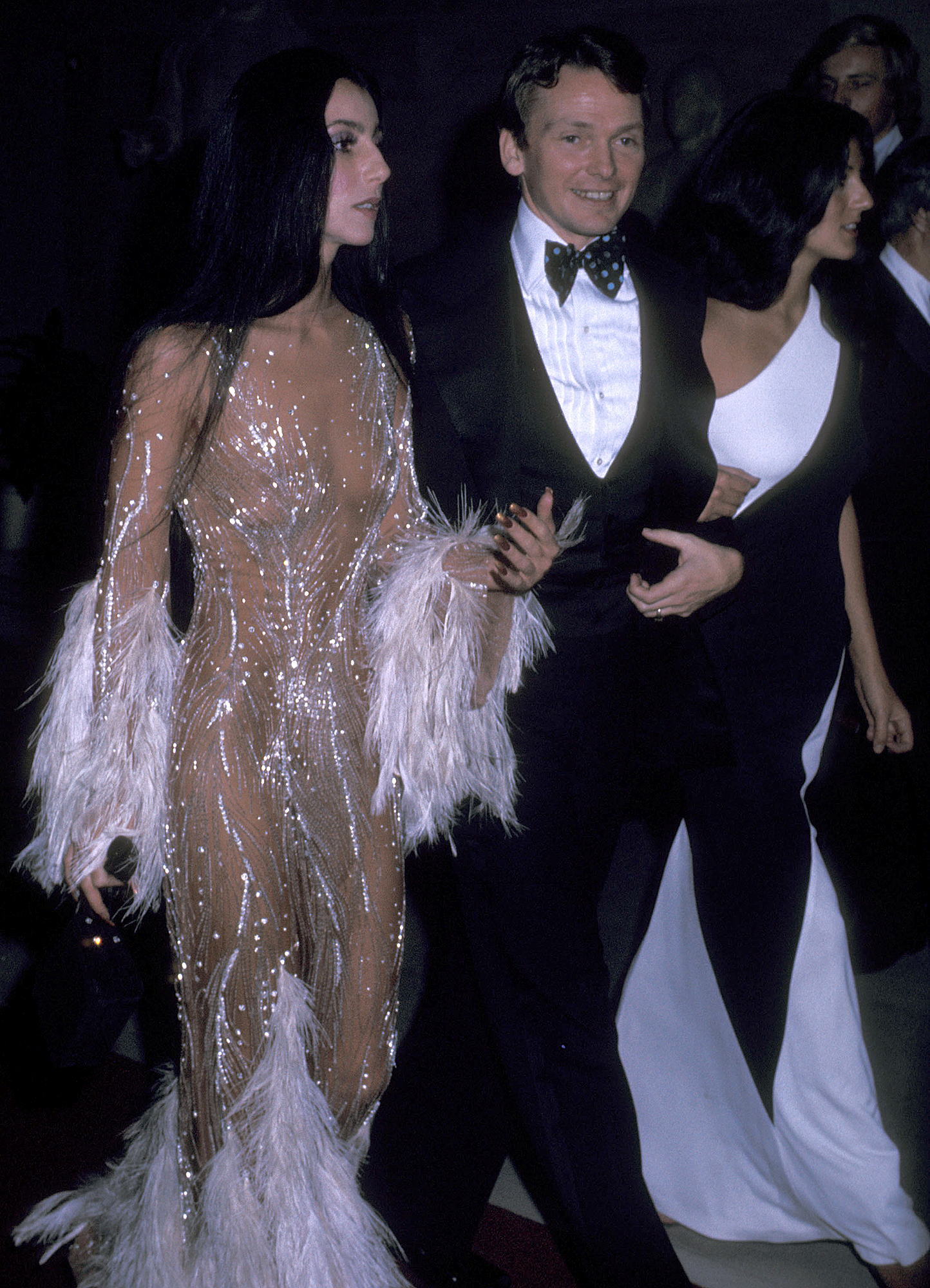 1974-cher - On the arm of the designer, the Moonstruck star stunned at the 3rd annual Met Gala in a sheer dress with white feathers and silver detailing.