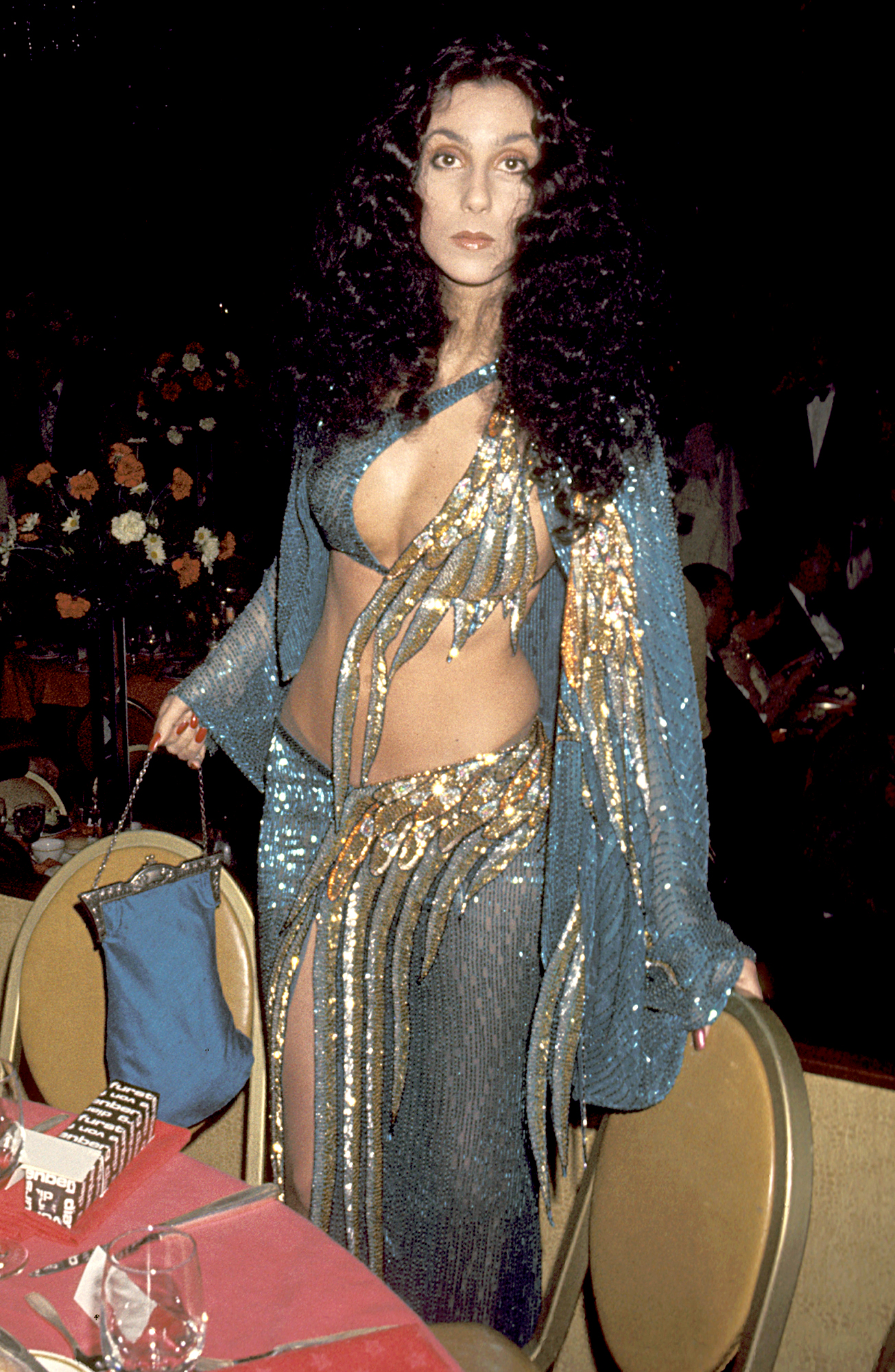 1977-Cher - At the Joseph Andrews L.A. premiere, the Grammy award-winning songstress wore a skirt and bra ensemble that was covered in blue and gold sequins.