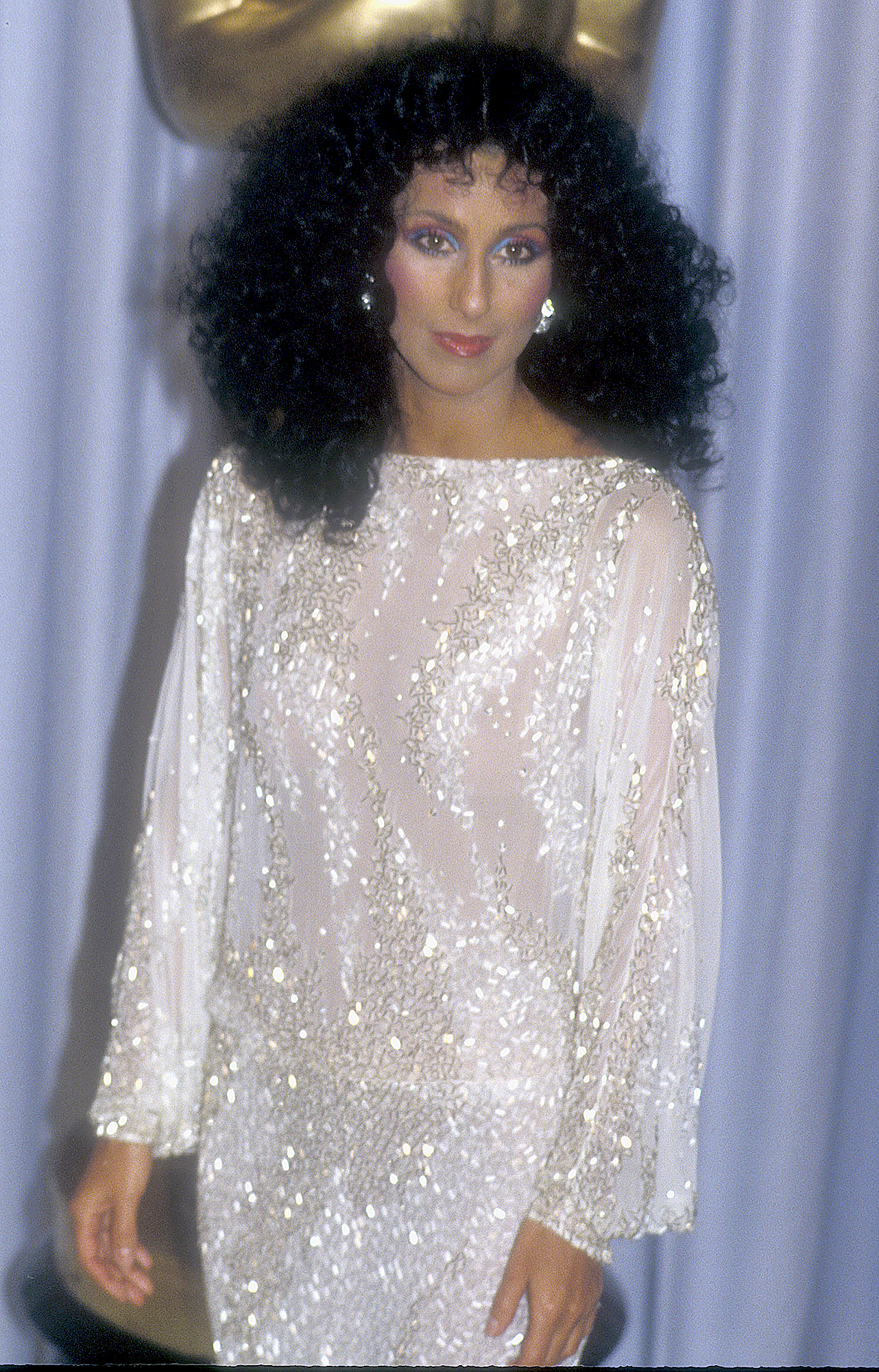 1983-Cher - As a presenter at the 55th annual Academy Awards, the award-winning artist wore yet another Mackie original that might not have bared her midriff but the long-sleeve white gown still showed skin with its see-through fabric.