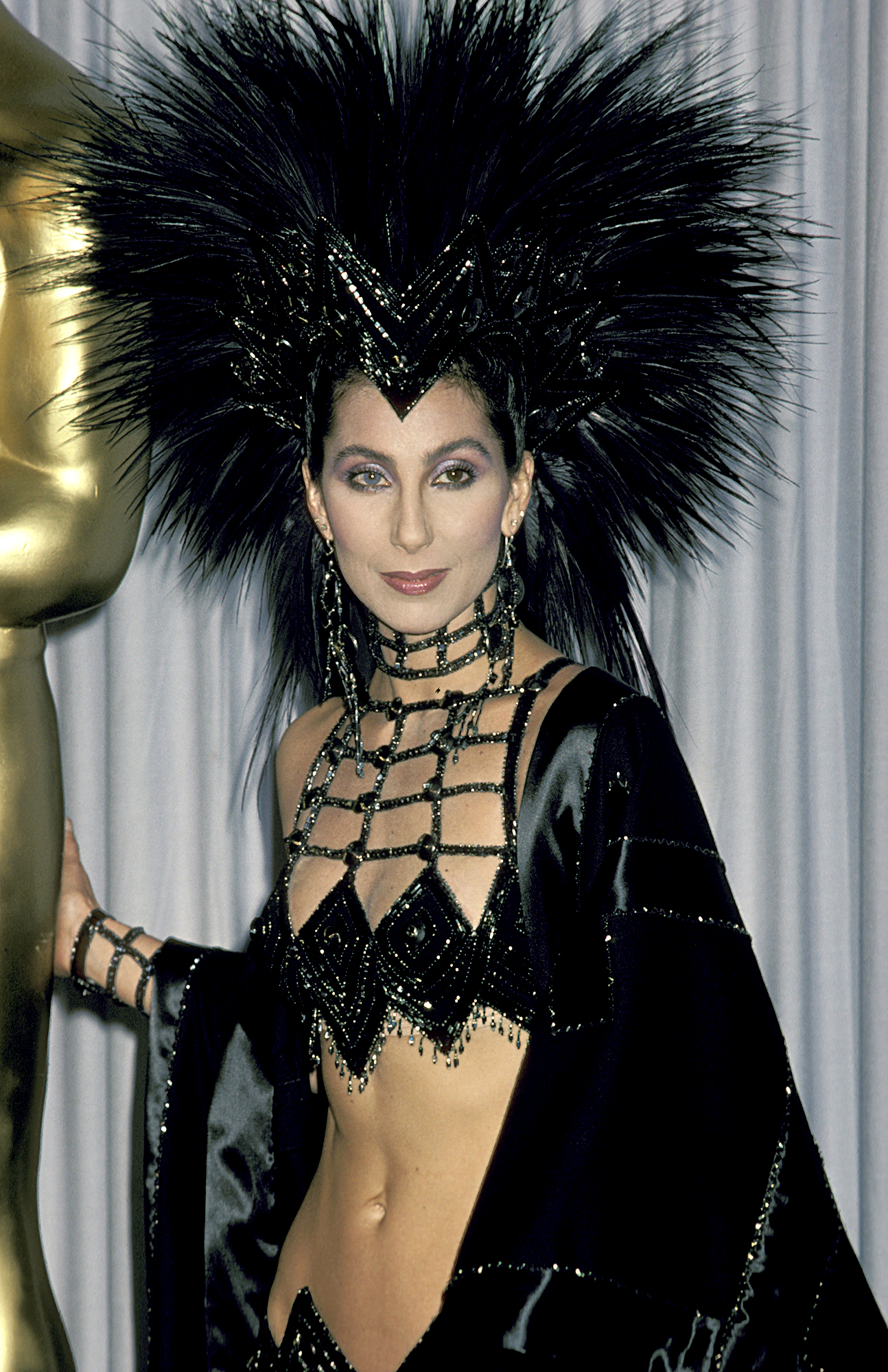 1986-Cher - Showing off her toned tummy, Cher looked statuesque at the Oscars in an embellished black gown and a giant feathered headpiece.