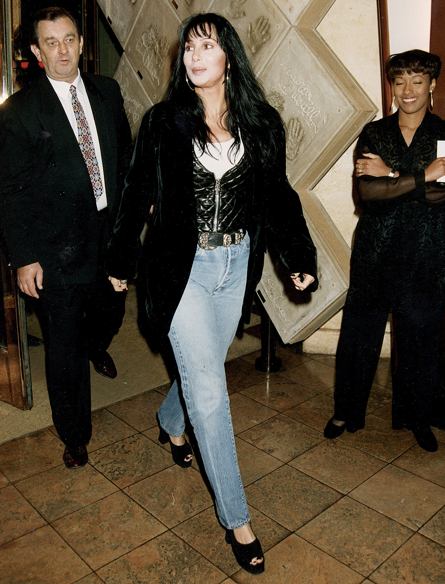 """1993-Cher - The epitome of chill '90s style, the """"Believe"""" singer stepped out in light-wash jeans, an oversized blazer and the same black leather vest she wore at the benefit in '94."""