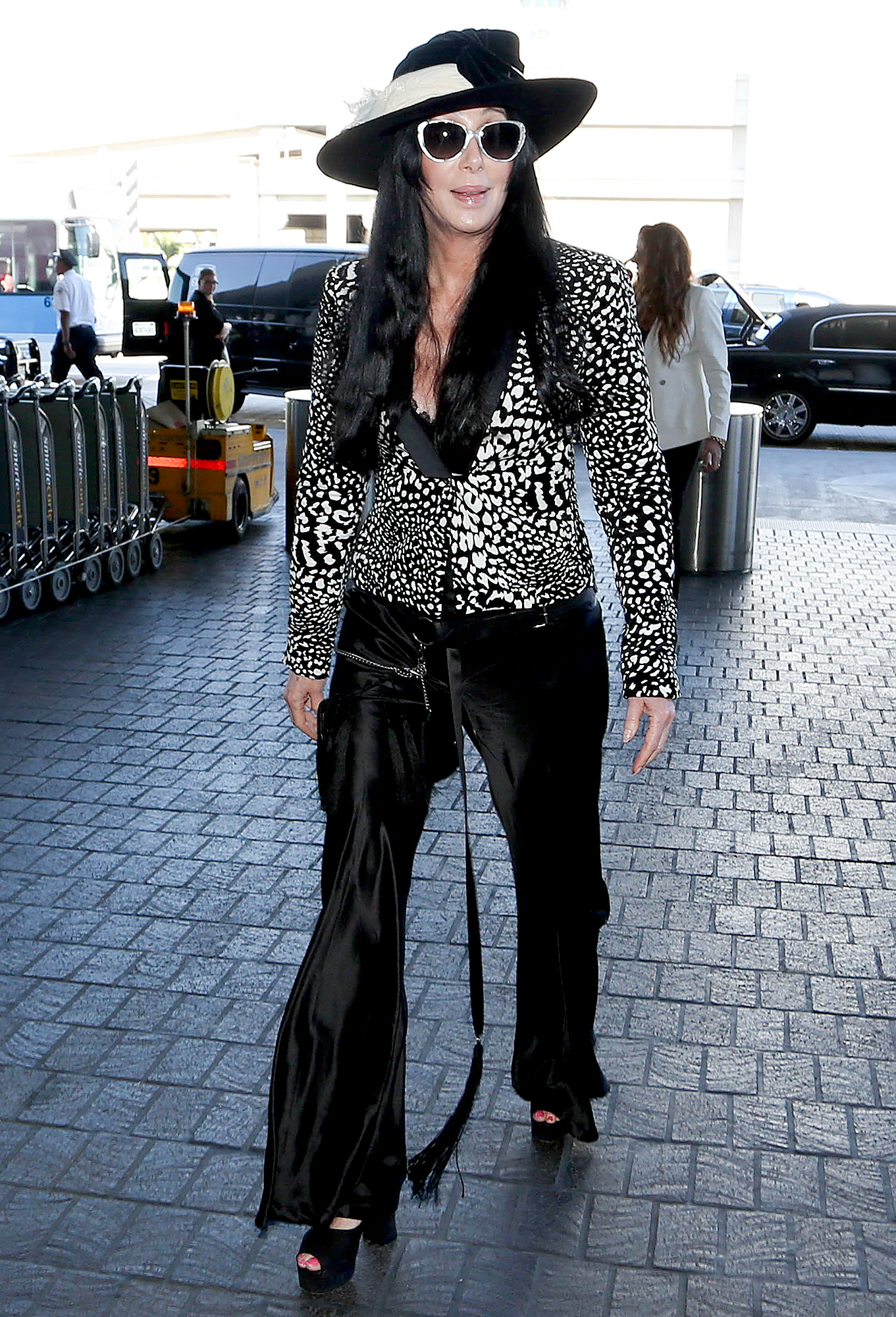 2015-2-cher - Even going to the airport, Cher adheres to her same sense of style looking cool in a hat, sunglasses, chunky heels and flared pants with a zipper pocket on one leg.