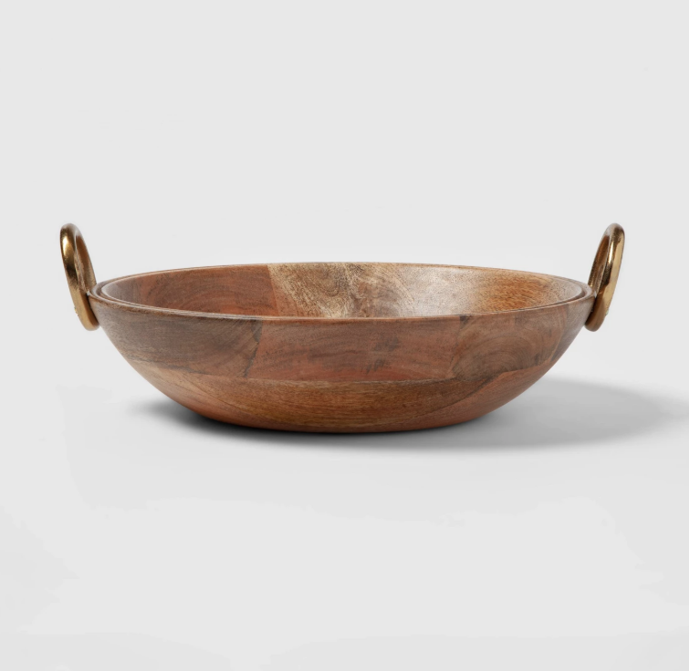 """13"""" Round Bowl with Aluminum Gold Handle Chrissy Teigen Explains Personal Significance Behind New Cravings Pieces - Teigen """"absolutely loves"""" this 13-inch wooden bowl. Though it can be used to serve food, the Lip Sync Battle cohost prefers to use it as a display piece. """"I usually fill it with lemons to brighten up my kitchen, but John loves to serve my spinach orzo salad in it,"""" she explained."""