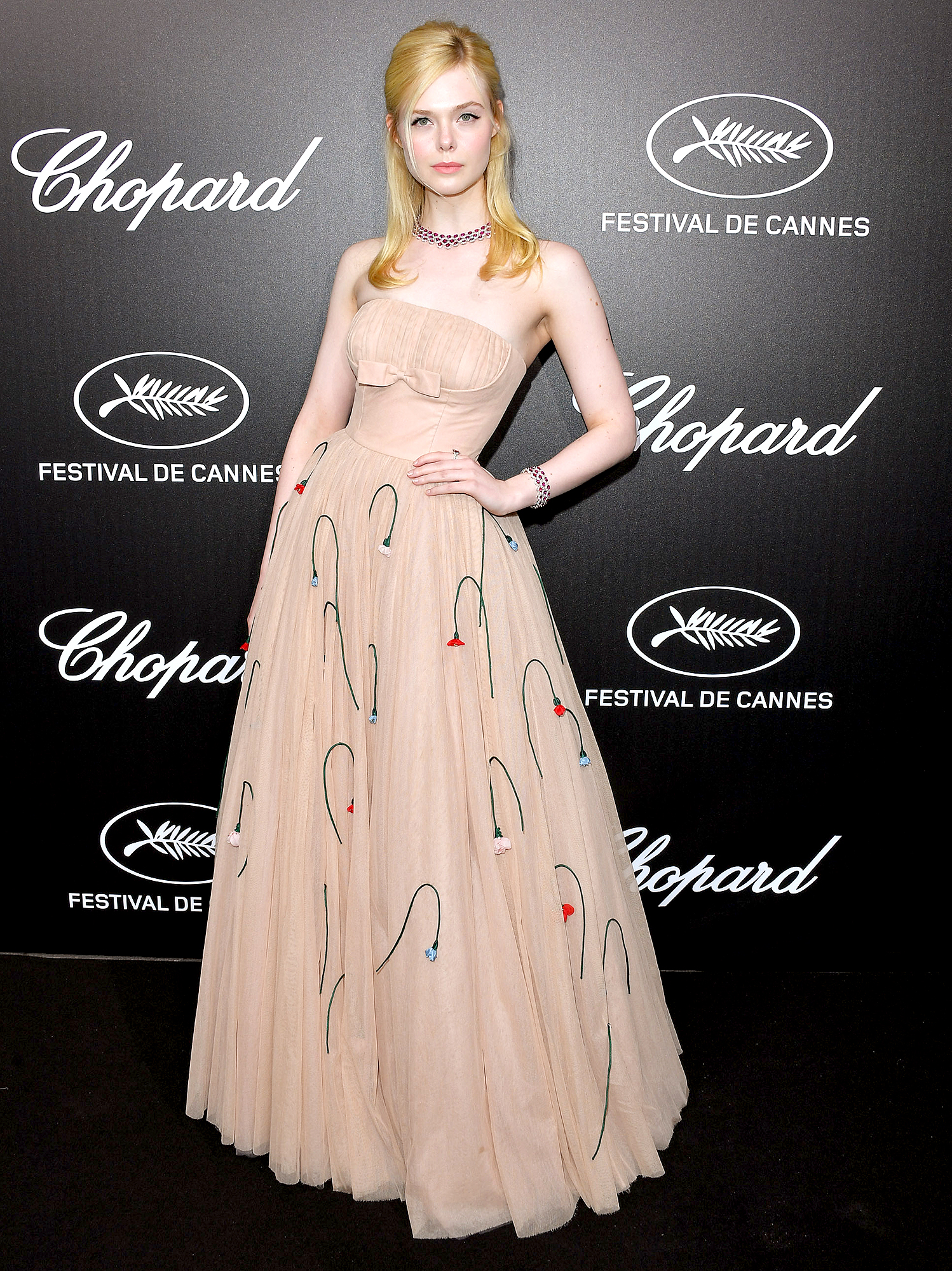 """Elle-Fanning - Before fainting and having Colin Firth come to her aid inside, the jurist arrived at the Chopard Trophy Event on Monday, May 20, in a strapless Prada gown and bling by the jeweler. """"Oops, had a fainting spell tonight in my 1950's Prada prom dress but it's all good!! #dresstootight #timeofthemonth,"""" she later shared on Instagram of the incident."""
