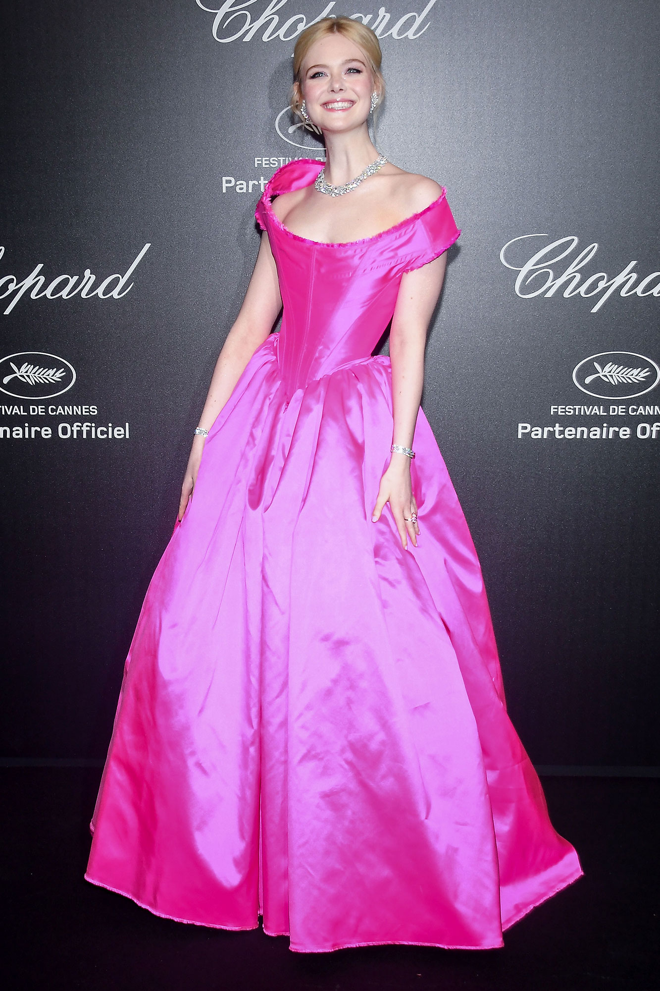 Elle Fanning Stepping Out in Style at Cannes Film Festival - Pretty in pink, indeed! The jurist brightened up the black carpet in a fuchsia Vivienne Westwood ball gown and Chopard bling at a party for the jeweler on Friday, May 17.