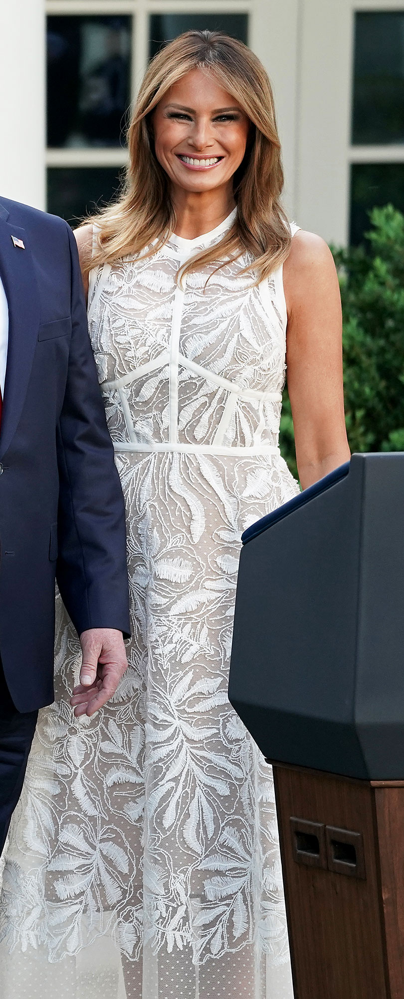 Melania Trump Takes a Page From Duchess Kate by Wearing This Designer - Attending Tiger Woods' Medal of Freedom ceremony in the Rose Garden at the White House, Mrs. Trump wore a $7,450 Elie Saab illusion mididress that she first debuted at the 2018 NATO Summit.