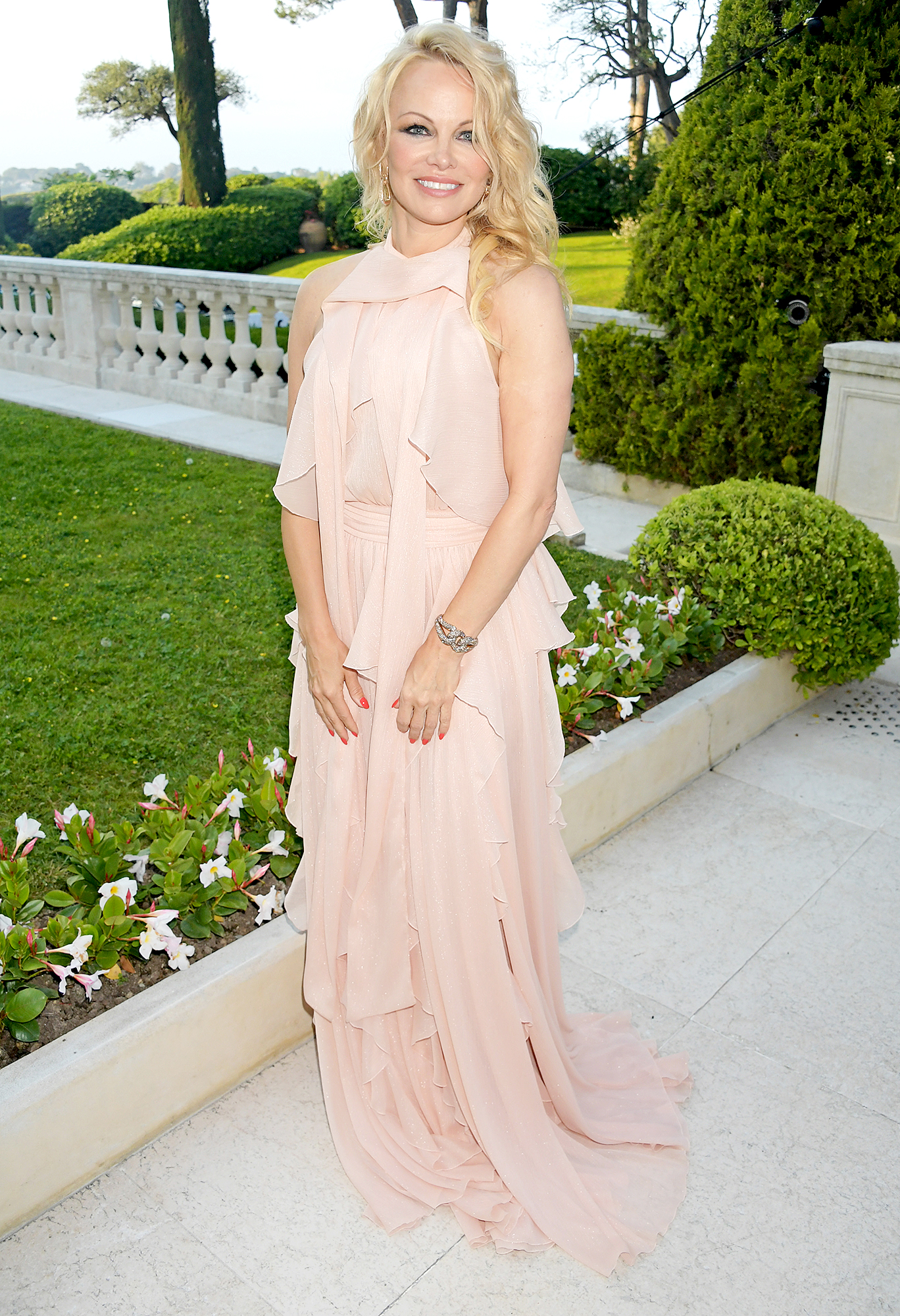 Pamela-Anderson - Beautiful in blush, the blonde beauty rocked a Grecian-inspired tiered number at the amfAR Cannes Gala on Thursday, May 23.