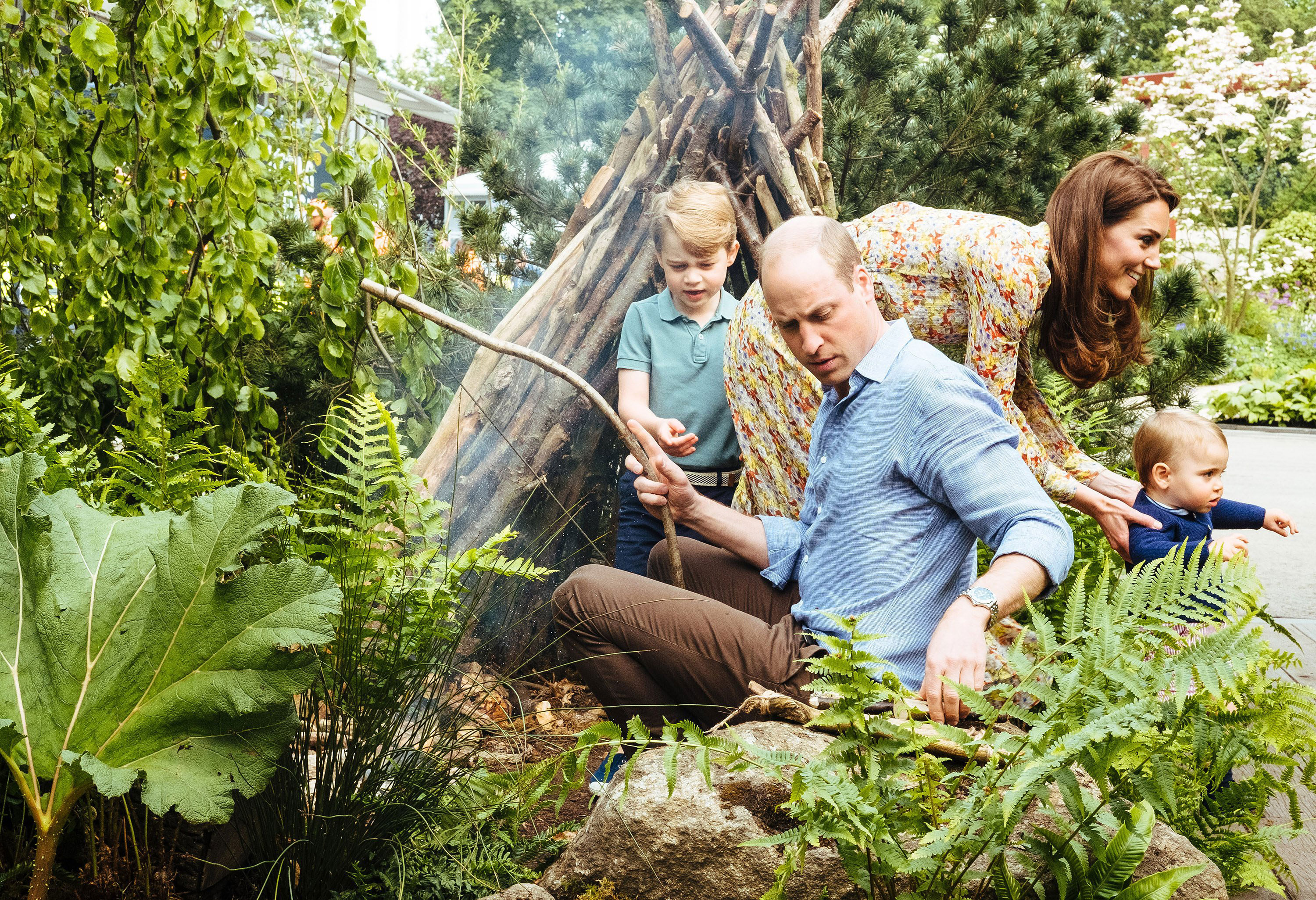 Prince William, Duchess Kate and Kids Play in the Garden She Designed at Chelsea Flower Show - William, 36, taught George how to make a fire while Kate held onto her youngest son.
