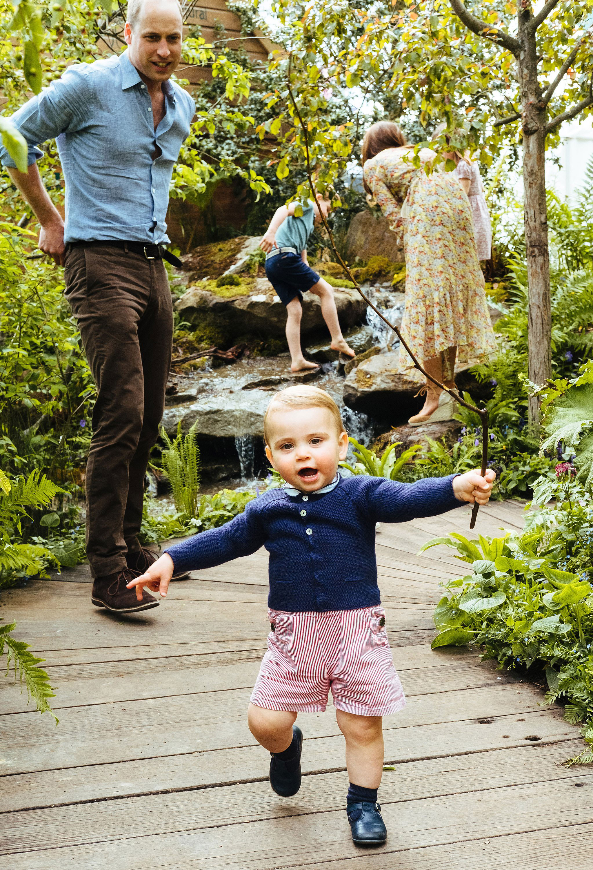 Prince William, Duchess Kate and Kids Play in the Garden She Designed at Chelsea Flower Show - Louis waved a stick as he charged down a wooden walkway.