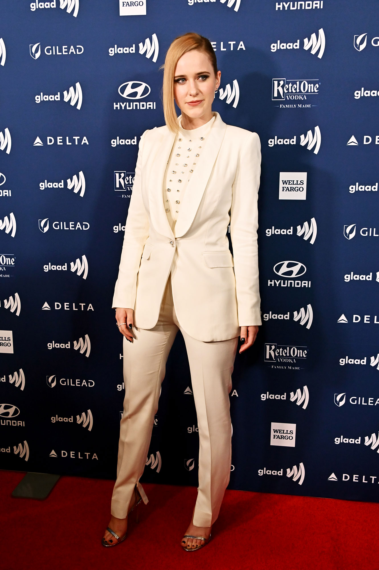 See the Stars at the GLAAD Awards Rachel Brosnahan - Wearing a white Ralph & Russo suit with Jimmy Choo sandals.