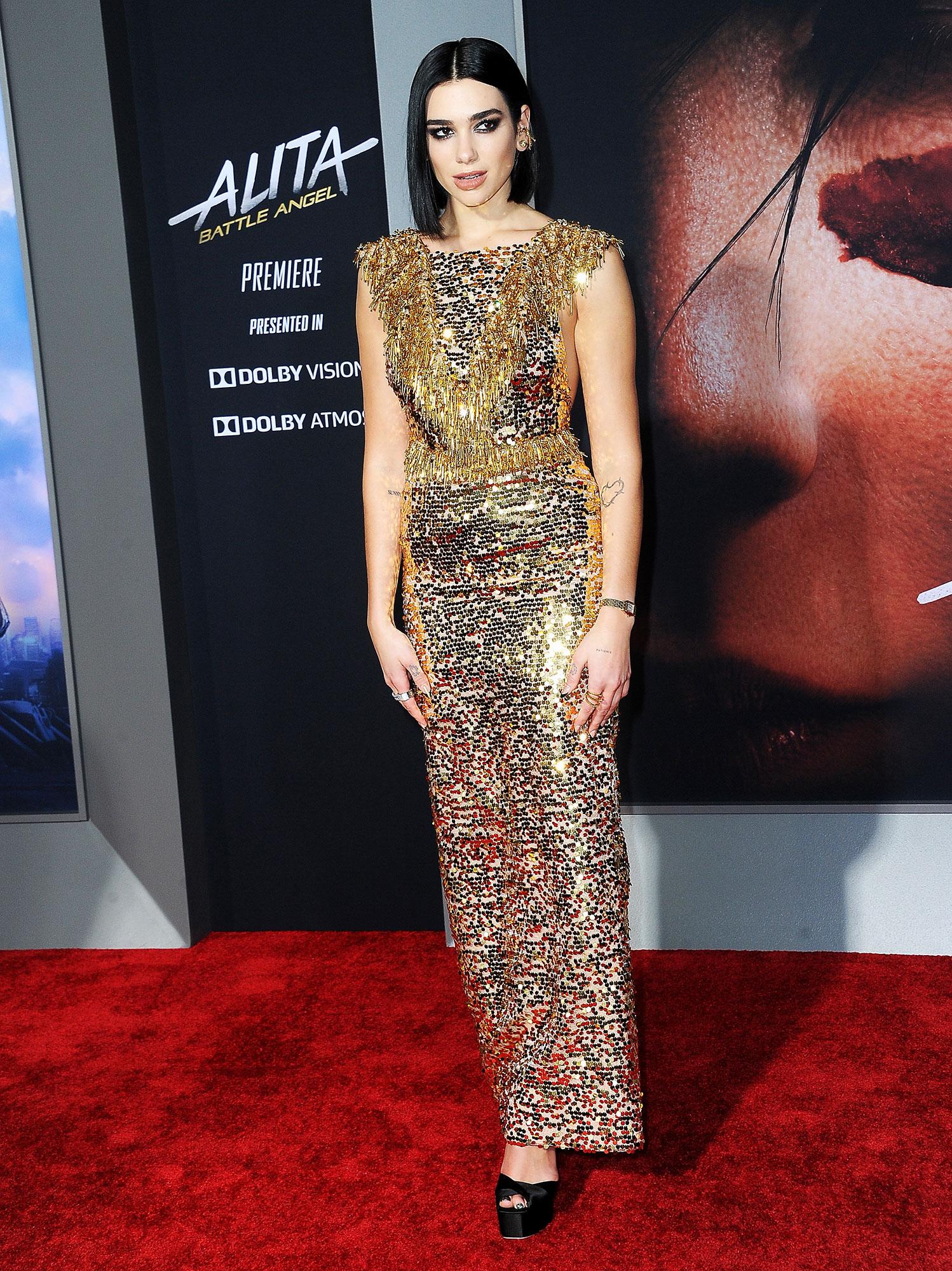 Dua Lipa stylish gold - In an organza fringe-accented Prada on Feb. 5.