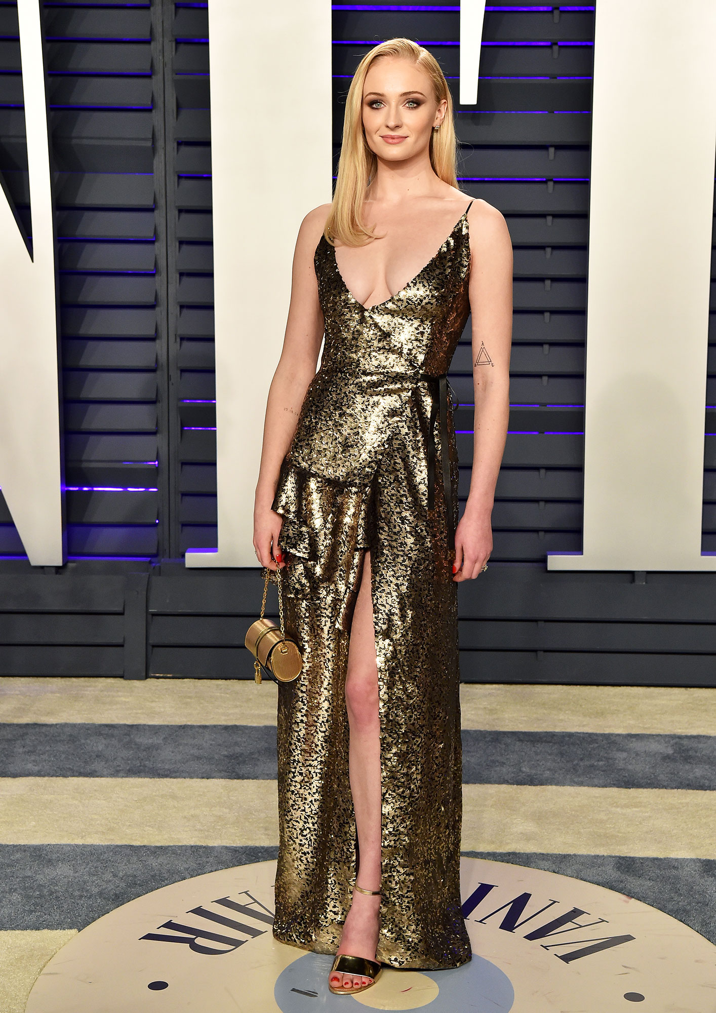 Sophie Turner stylish gold - In a high-slit sequin Louis Vuitton on Feb. 24.