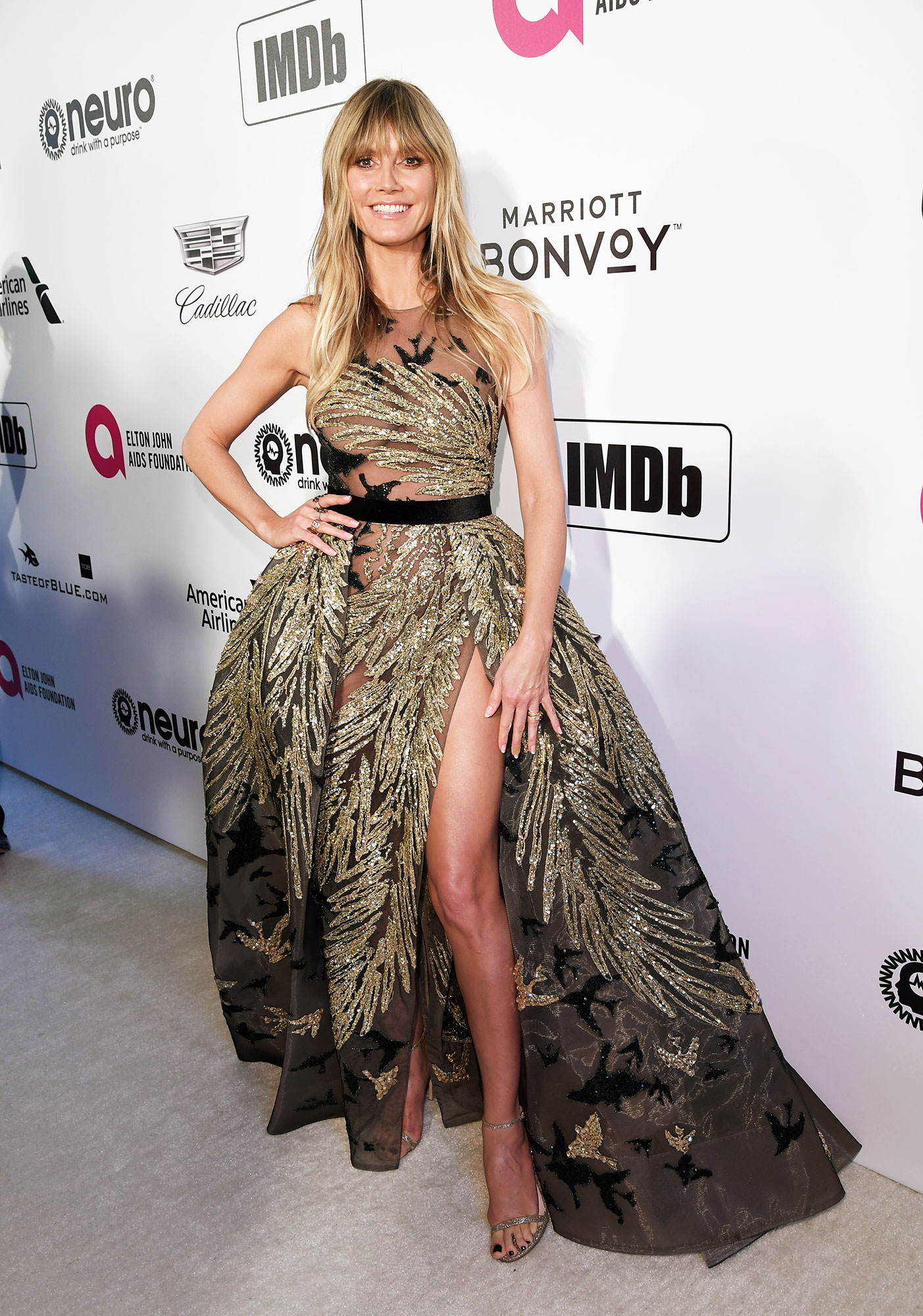 Heidi Klum stylish gold - In a sequin and feather Elie Saab on Feb. 24.