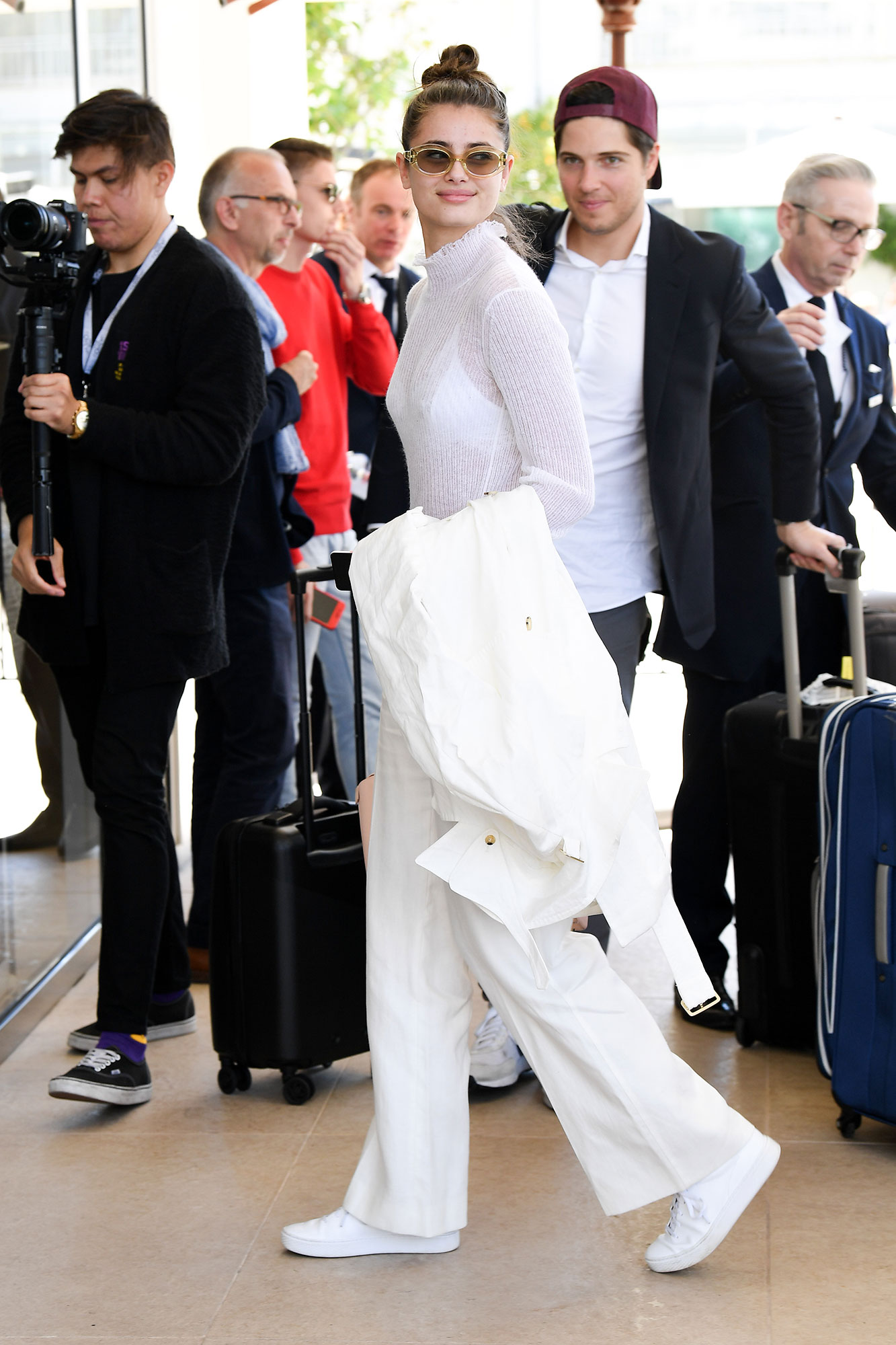 Taylor Hill Memorial Day White - On May 16, 2019, the model wore clean sneaks, flared pants and a sheer sweater that appeared sophisticatedly yet relaxed.