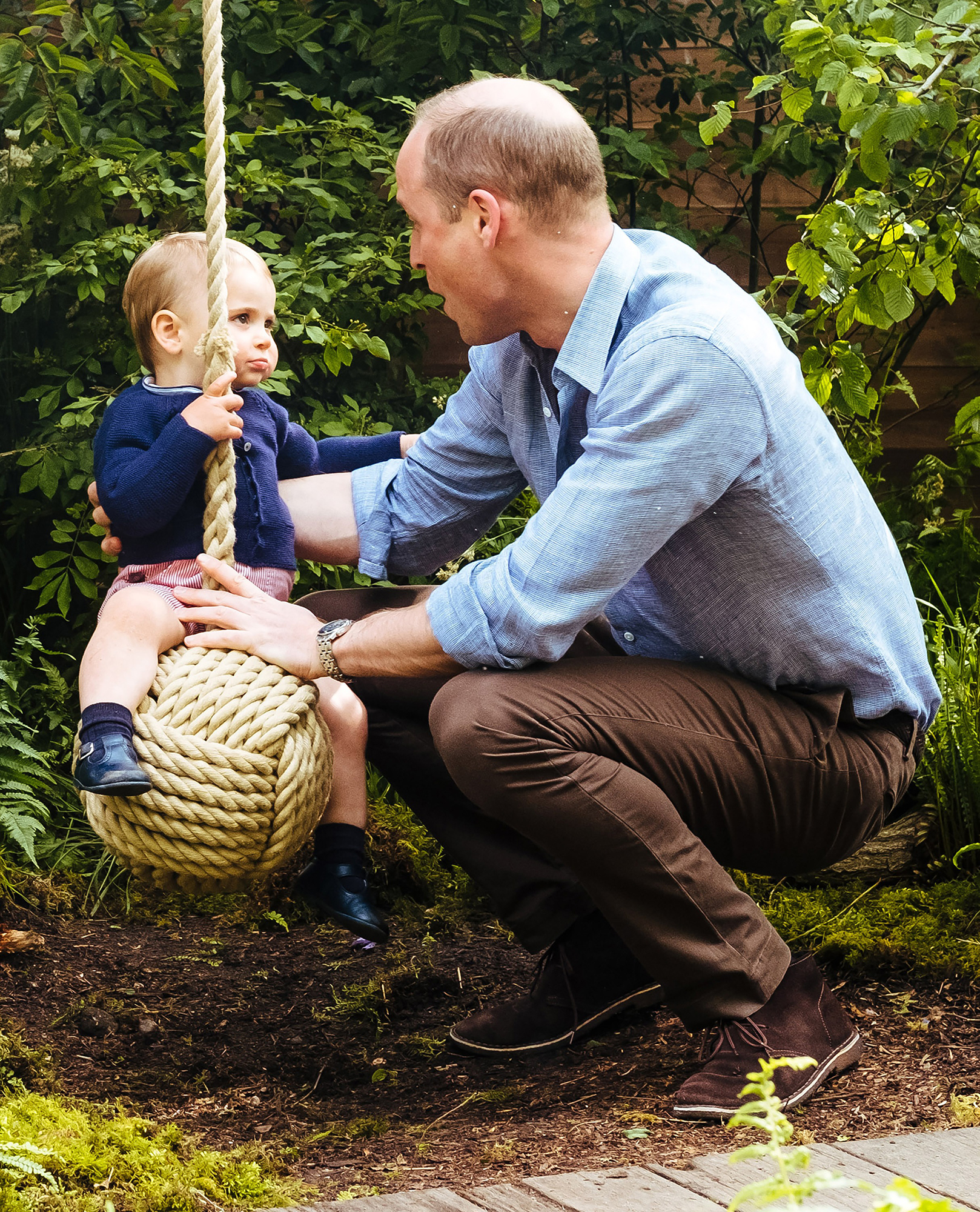 Prince William and Louis Chelsea Flower Show - Louis sat on a rope swing with his dad's help at the Chelsea Flower Show garden his mom designed in May 2019.