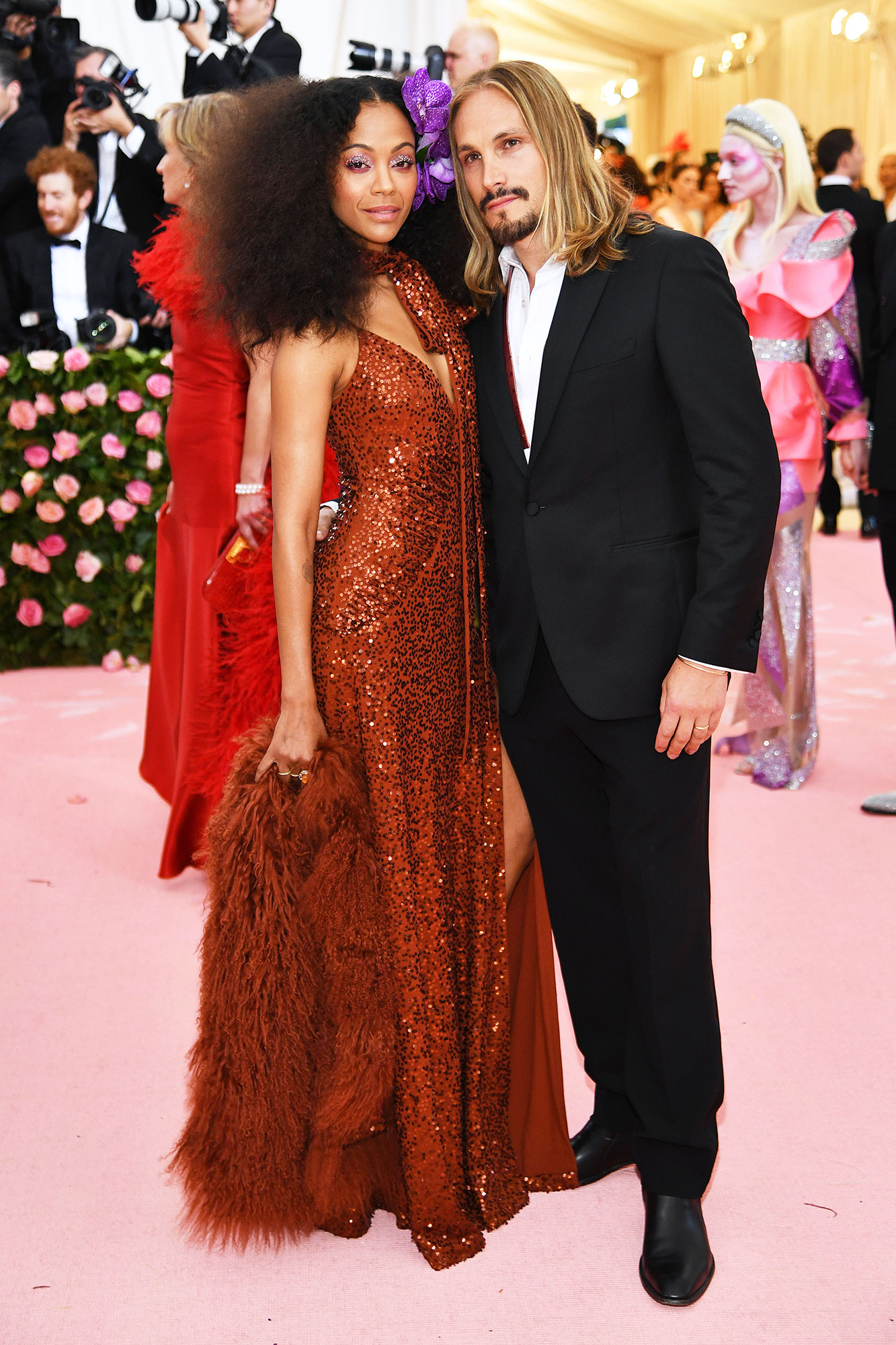 Zoe Saldana and Marco Perego met gala 2019 couples - The actress stunned in a burnt orange Michael Kors Collection gown, which her hubby paid homage to with his tie.