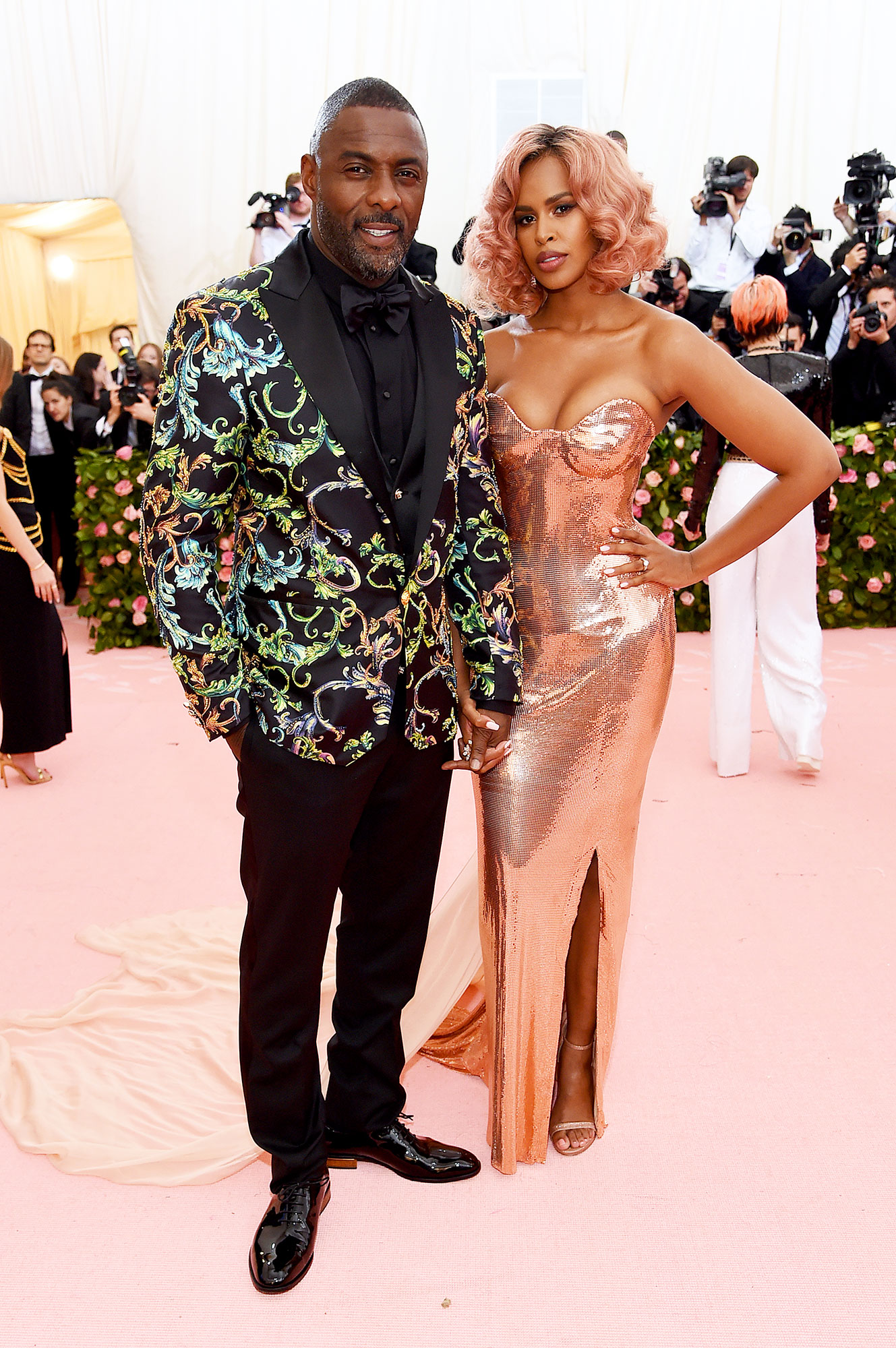 Idris Elba and Sabrina Dhowre met gala 2019 couples - Basking in that newlywed glow, the actor rocked a paisley-print jacket, while his bride stunned in a liquid metal rose gold gown (and matching hair!).