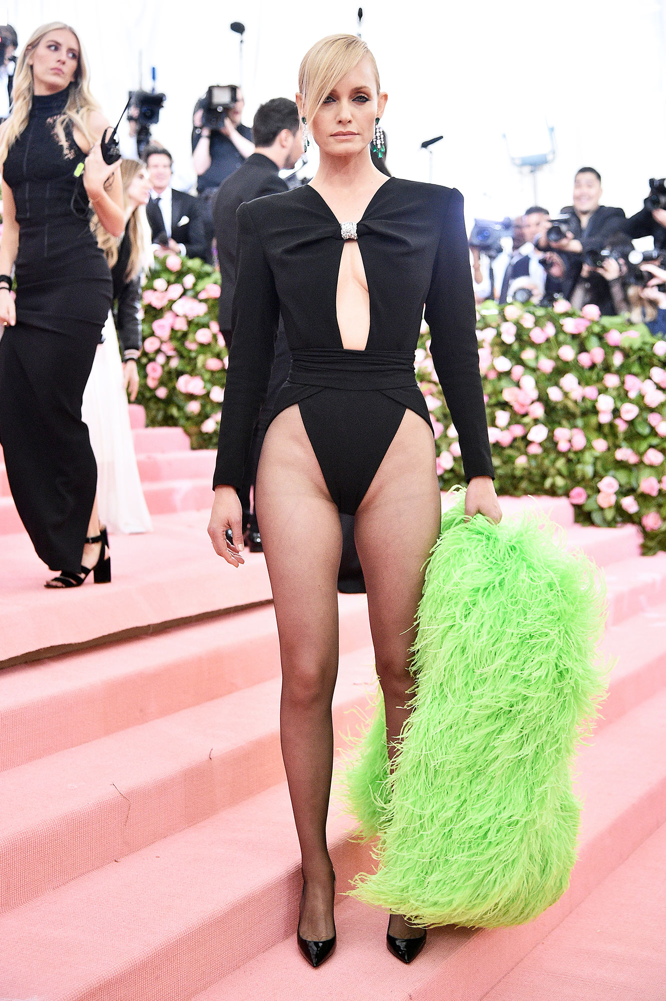 Amber Valletta met gala 2019 - Wearing a black leotard with a featherd green jacket and Chopard jewels.