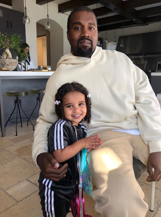 Kayne West Wearing a White Hoodie Holding Dream