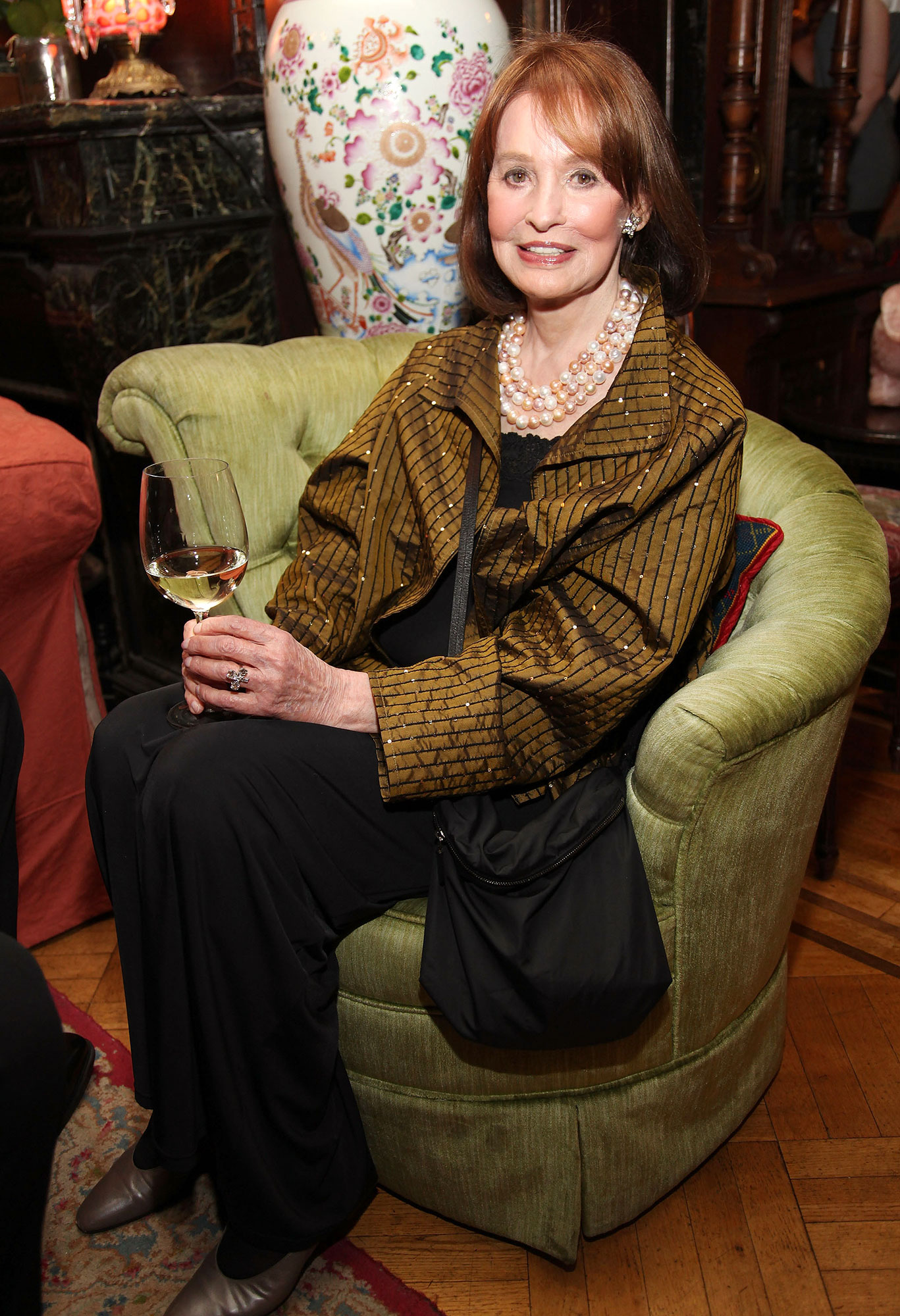 Gloria Vanderbilt Sitting Drinking a Glass of Wine