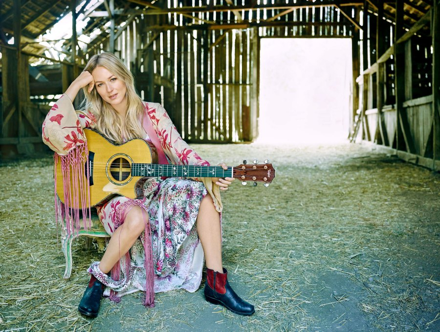 Jewel Holding Guitar in Dress Sitting in a Barn With Hay on the Floor