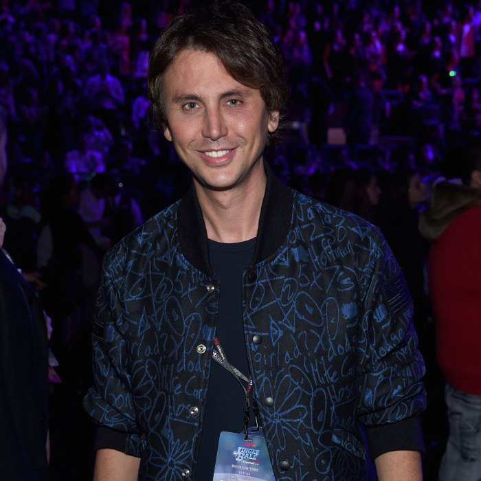 Jonathan Cheban attends Jingle Ball in a black jacket with a blue pattern on it.
