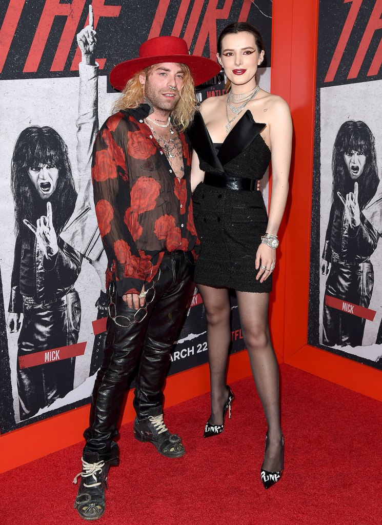 Mod Sun Wearing Black Leather Pants and Red Shirt with Red Brim Hat and Bella Thorne Wearing Black Dress