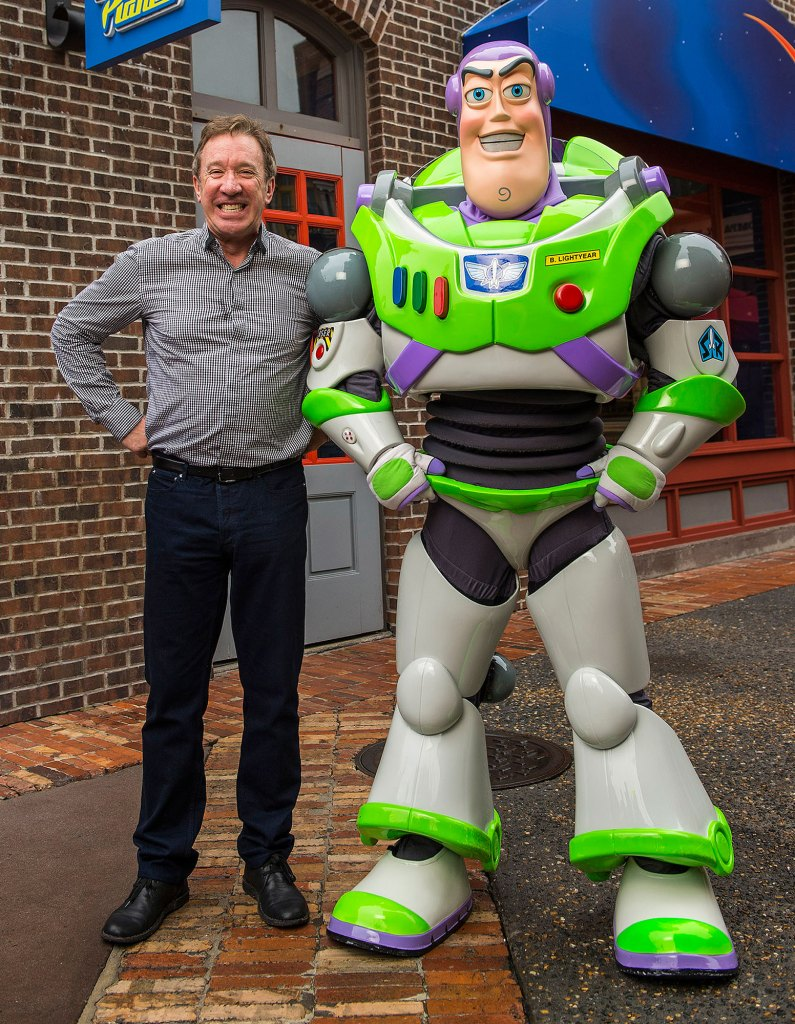 Tim Allen Poses With His Hands on His Hips Next To Buzz Lightyear With A Giant Grin