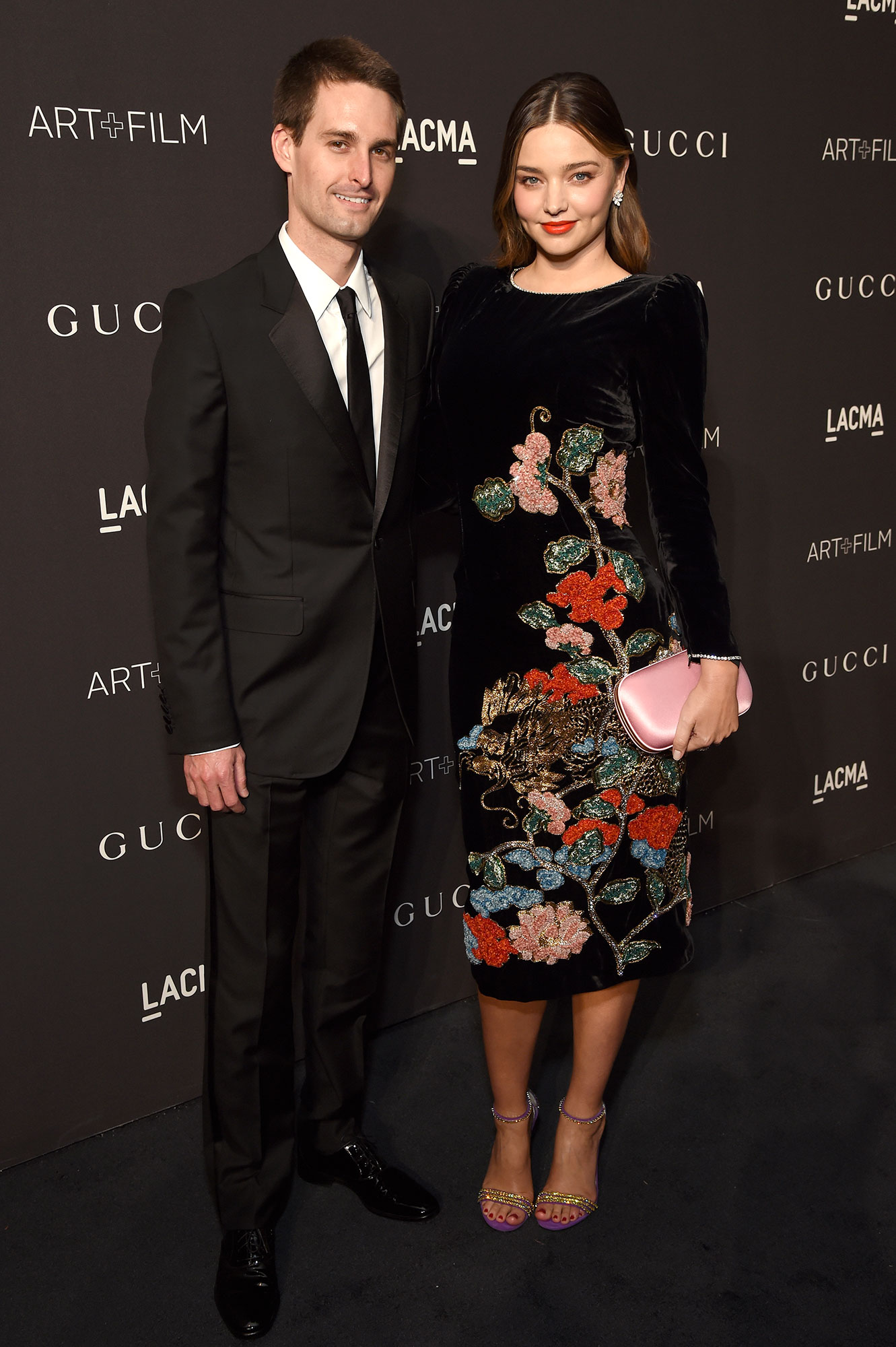 Evan Spiegel and Miranda Kerr Inside Pregnant Life Black Suit Black Dress WIth Flowers and Pink Hand Bag Purse - Evan Spiegel and Miranda Kerr attend 2018 LACMA Art + Film Gala honoring Catherine Opie and Guillermo del Toro presented by Gucci at LACMA on November 3, 2018 in Los Angeles, California.