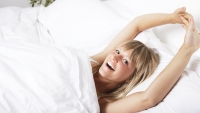 Smiling young woman stretching in bed
