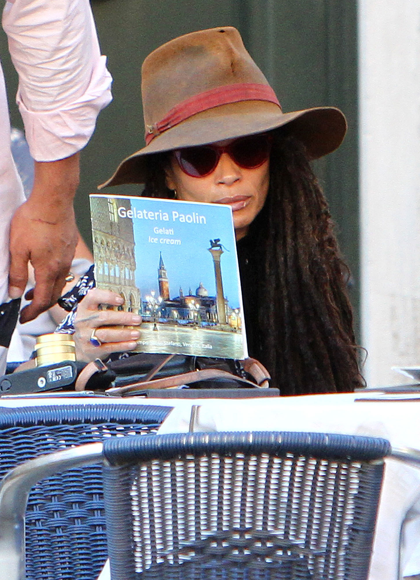 Lisa Bonet Explore Italy Brown Rim Hat Reading - Bonet pondered her options as the family took a gelato break at a local restaurant.