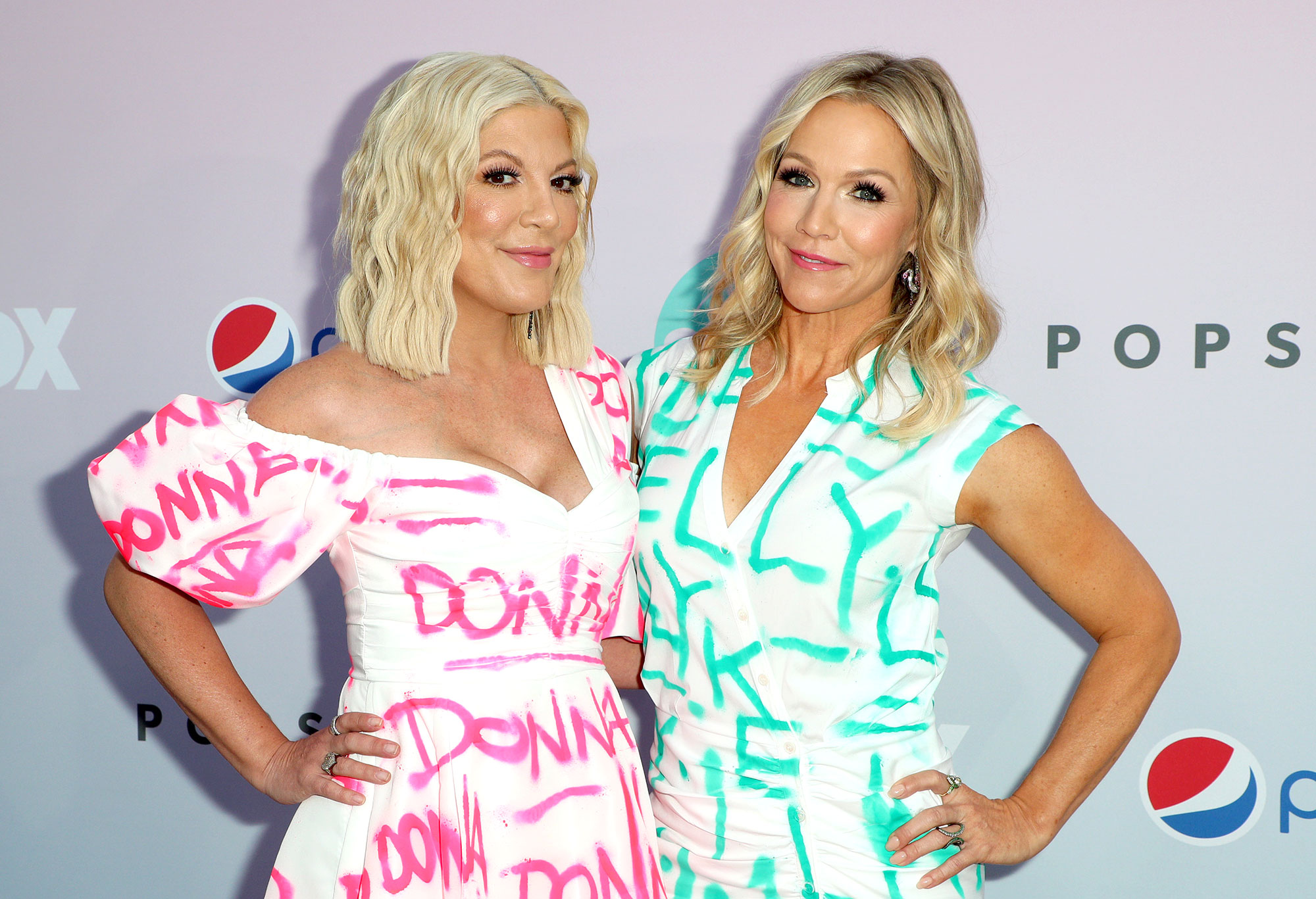 Tori Spelling and Jennie Garth Wearing Clothes With Donna and Kelly Written on Them Say Aaron Spelling Would Be Proud BH90210 - Tori Spelling and Jennie Garth arrive at the BH90210 Peach Pit Pop-Up on August 3, 2019 in Los Angeles, California.