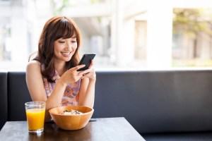 Contenu fille souriante regardant l'écran du téléphone dans ses mains