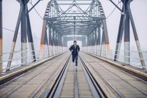 Shot of a male running on the train bridge.