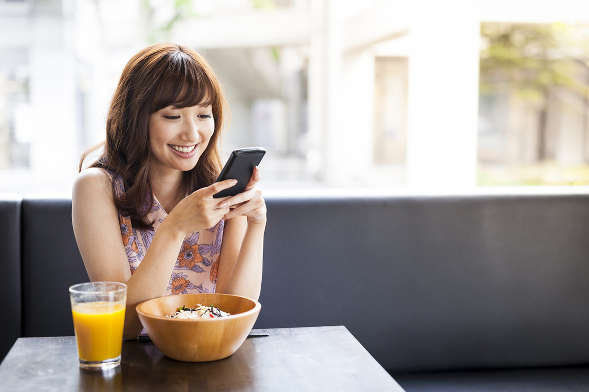 woman eating using phone