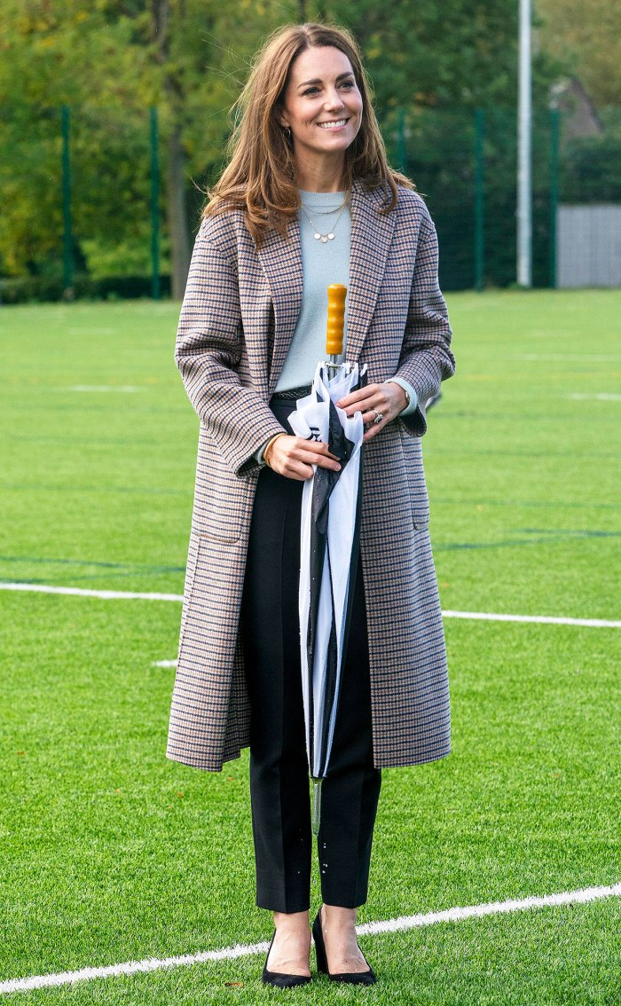 Duchess Kate Visiting The University Of Derbvy In A Plaid Coat And Carrying An Umbrella