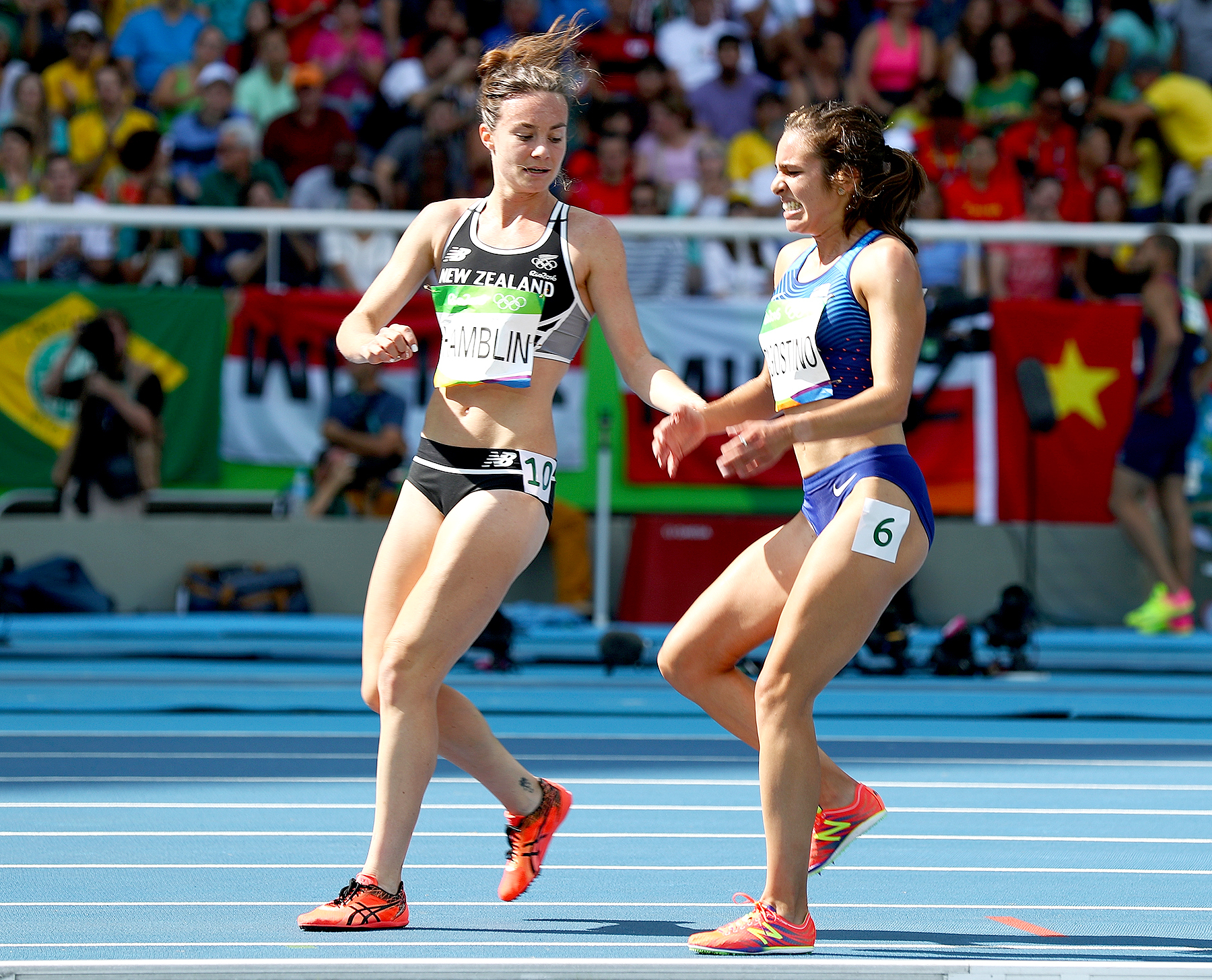 Abbey D'Agostino of the United States (R) is assisted by Nikki Hamblin of New Zealand after a collision during the Women's 5000m Round 1 - Heat 2 on Day 11 of the Rio 2016 Olympic Games at the Olympic Stadium on August 16, 2016 in Rio de Janeiro, Brazil.