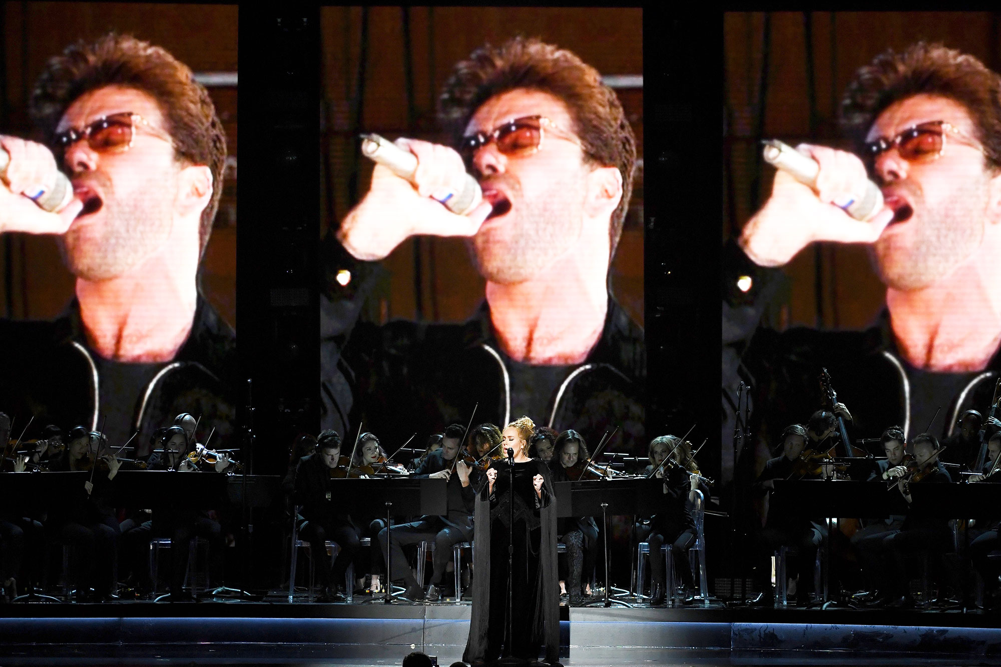 An image of the late George Michael is projected on a video screen while recording artist Adele performs on stage.