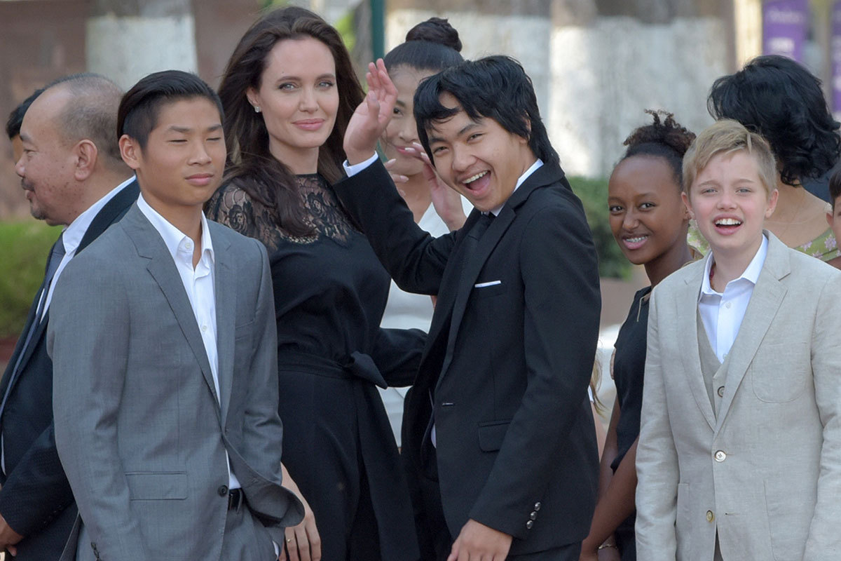 Hollywood star Angelina Jolie (3rd L) and her children including Maddox Jolie-Pitt (C) gesture to media in front of the royal residence for a meeting with Cambodian King Norodom Sihamoni in Siem Reap on February 18, 2017