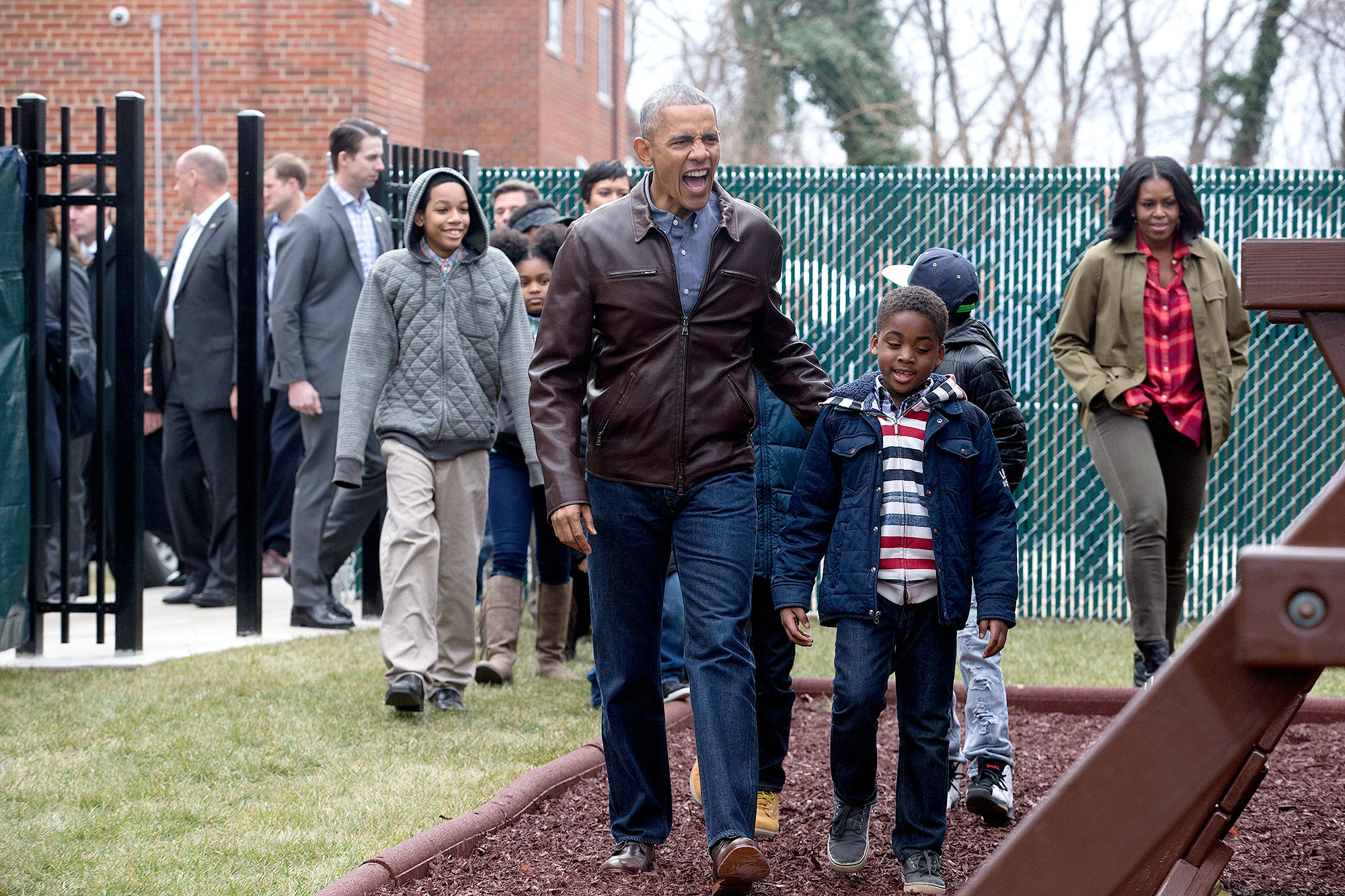 U.S. President Barack Obama and first lady Michelle Obama arrive with children to play on a playset dubbed Malia and Sasha's Castle, formerly used by the Obama children at the White House and donated by the Obama family, during a service marking Martin Luther King Jr. Day at the Jobs Have Priority Naylor Road Family Shelter January 16, 2017 in Washington, DC.
