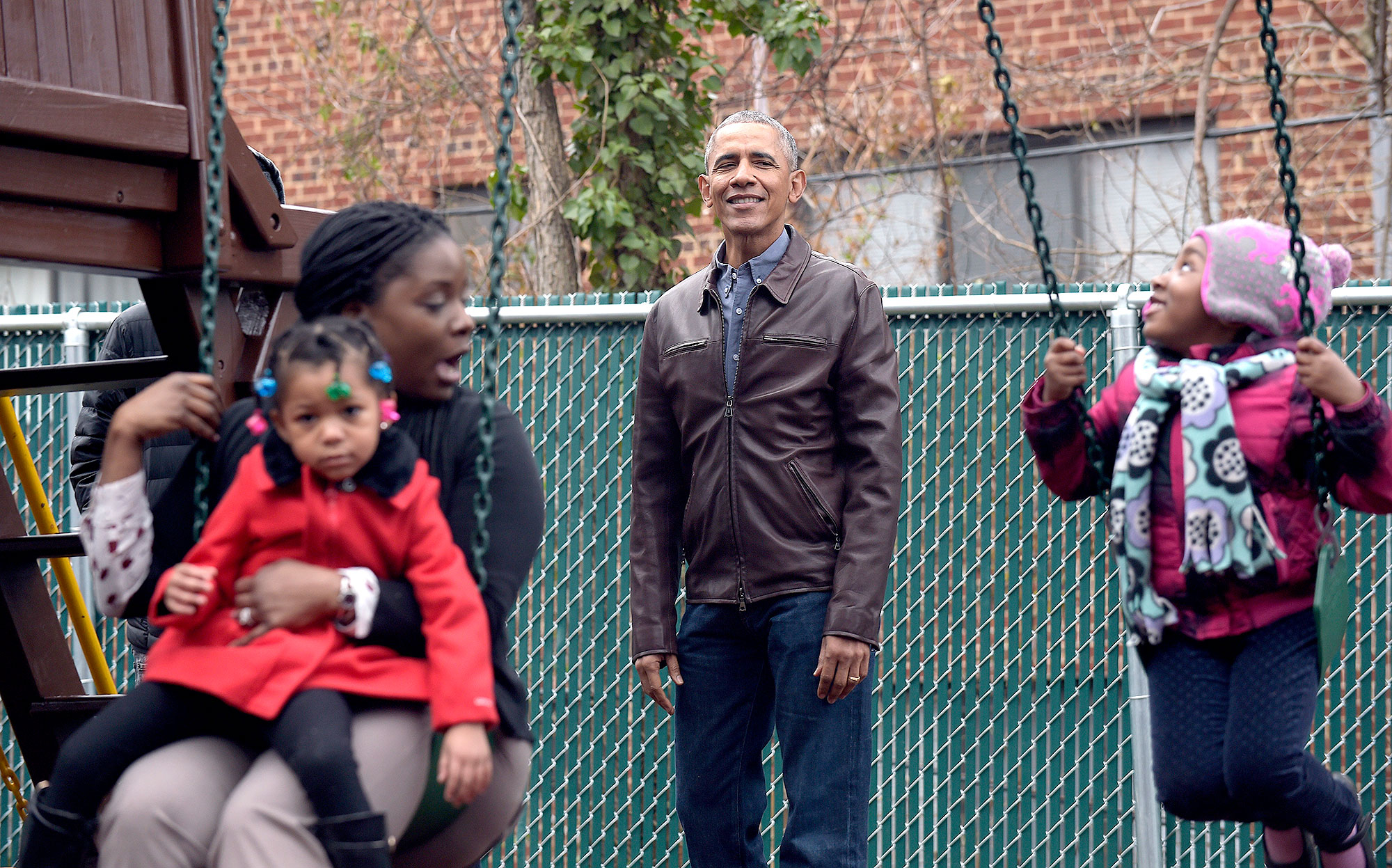 President Barack Obama watches as children play on the