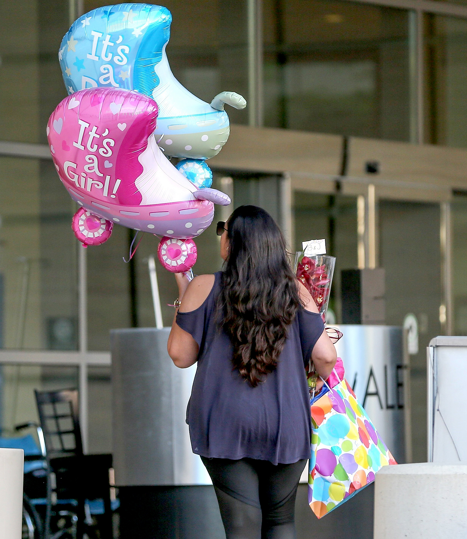 "A woman is seen heading into the hospital holding balloons welcoming a girl and a boy, along with flowers, a gift bag, and a card that reads ""B & J,"" on June 17, 2017."