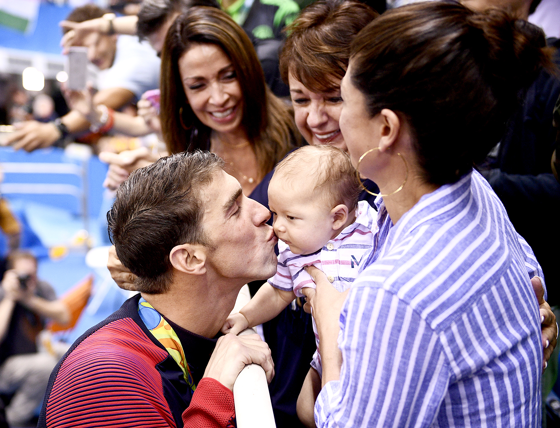USA's Michael Phelps kisses his son, Boomer, next to his fiancée, Nicole Johnson (R) and mother Deborah (C) after he won the men's 200-meter butterfly final at the Rio 2016 Olympic Games at the Olympic Aquatics Stadium in Rio de Janeiro on August 9, 2016.