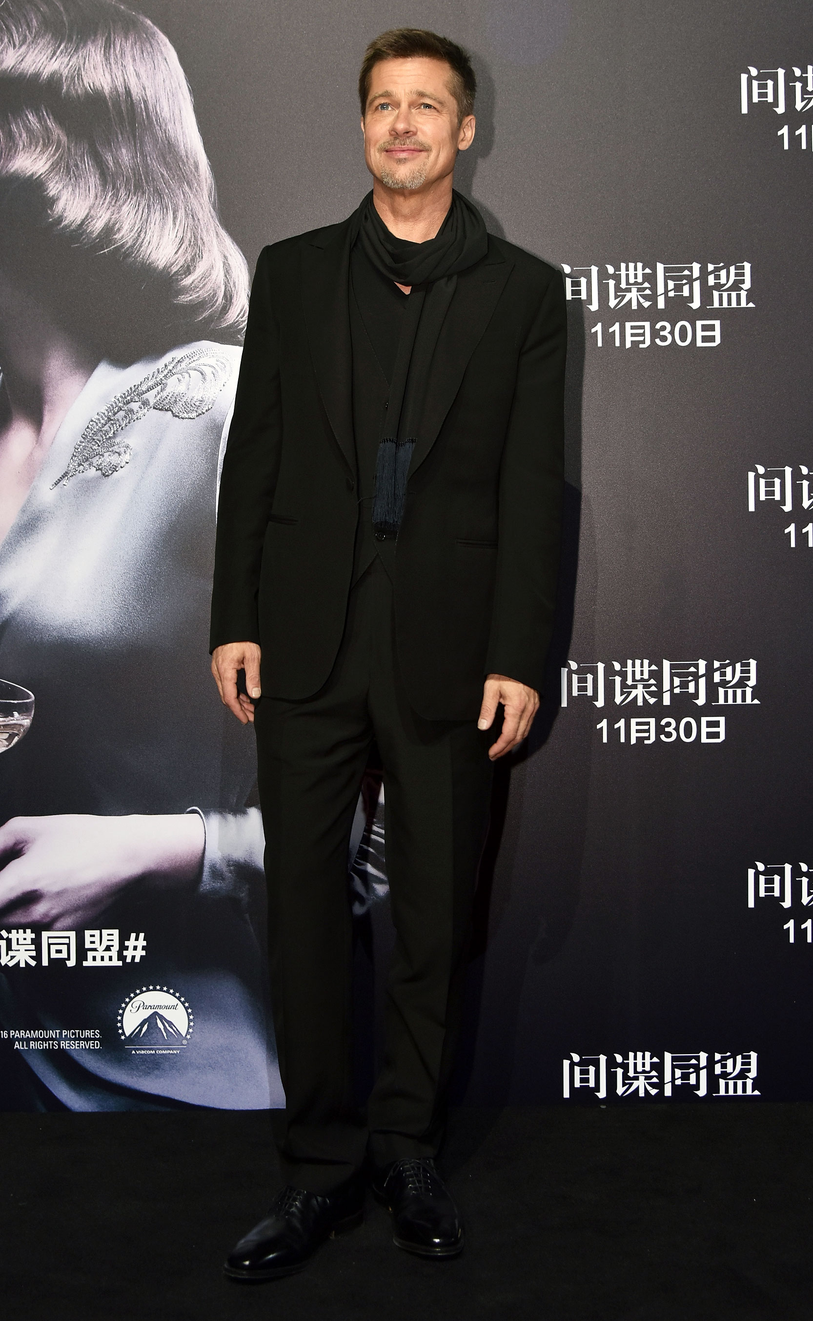 brad pitt - Pitt continued his press tour for Allied showing up for the premiere in Shanghai on November 14, 2016 in an all-black suit, with a black T-shirt underneath and a black scarf with navy tassels on the end.