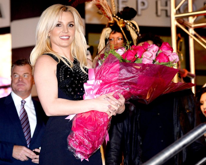 Britney Spears holds a bouquet of flowers at a welcome ceremony as she celebrates the release of her new album