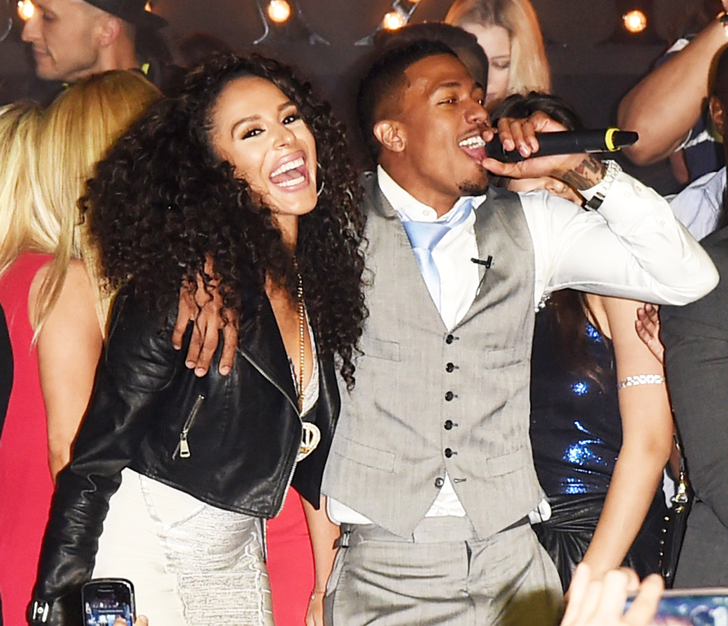 Brittany Bell and Nick Cannon perform onstage during the Maxim Party on January 31, 2015 in Phoenix, Arizona.