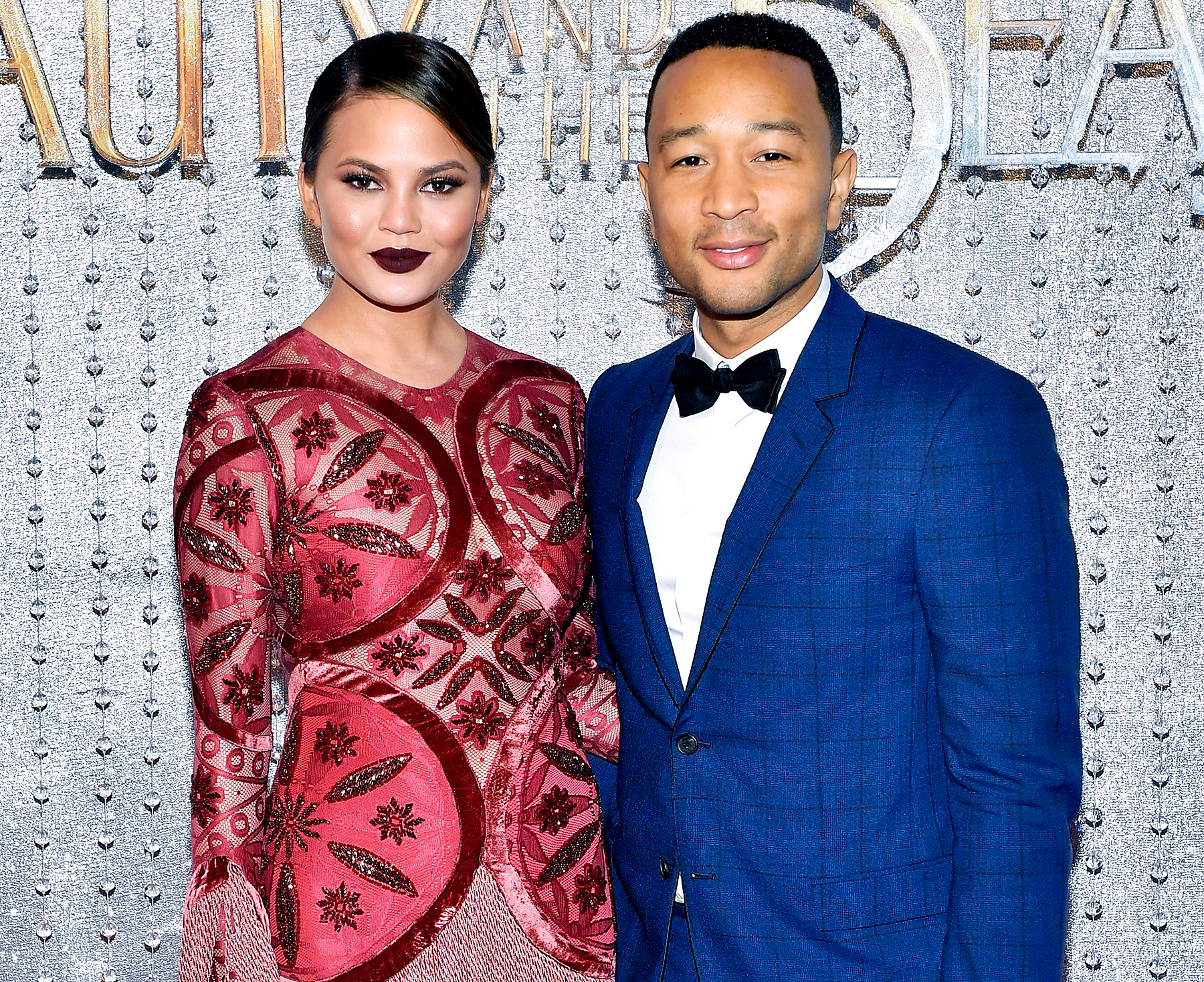 """Chrissy Teigen and John Legend arrive at the world premiere of Disney's new live-action """"Beauty and the Beast"""" photographed in front of the Swarovski crystal wall at the El Capitan Theatre on March 2, 2017 in Hollywood, California."""