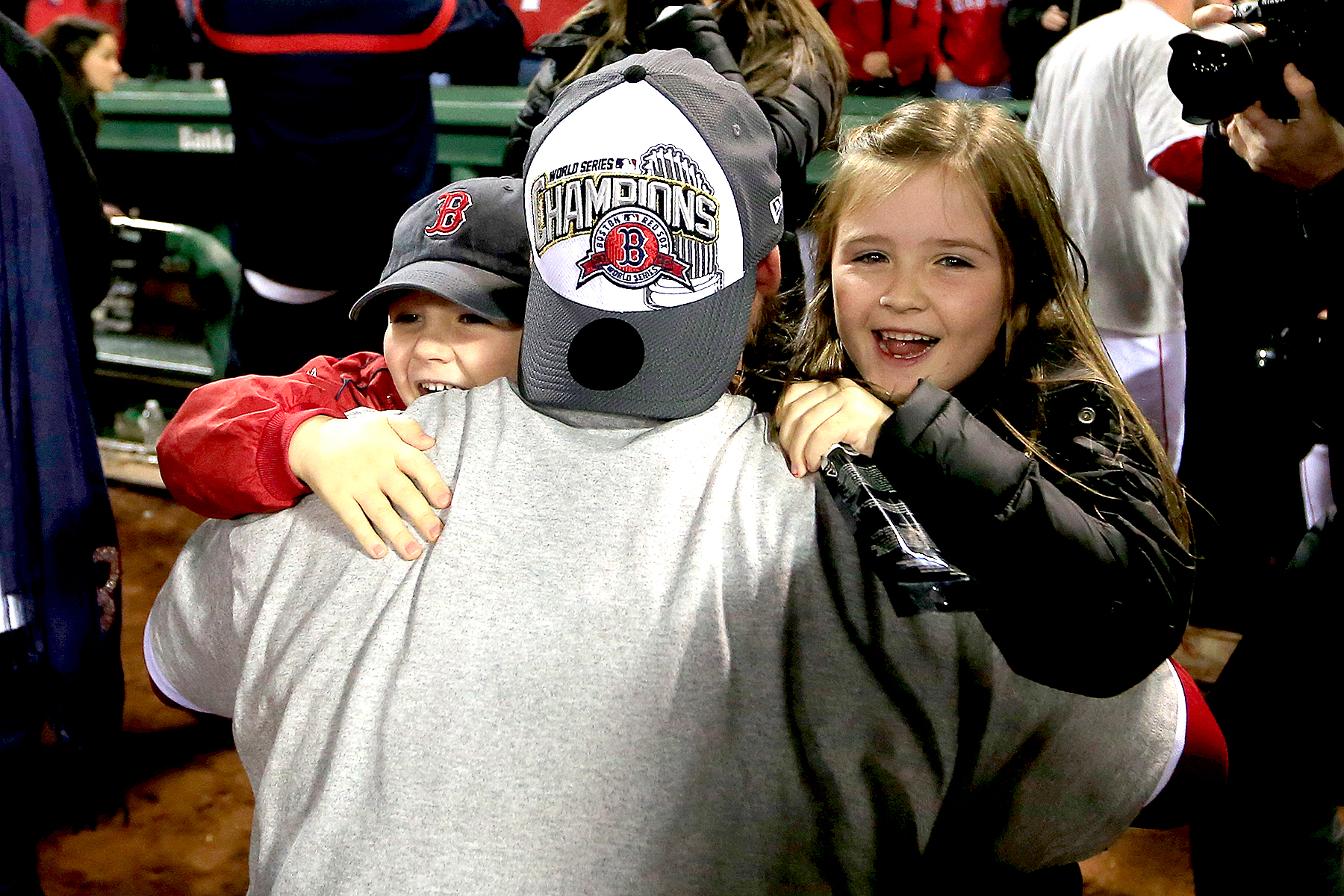 David Ross #3 of the Boston Red Sox hugs his children Landri (R) and Cole (L) following a 6-1 victory over the St. Louis Cardinals in Game Six of the 2013 World Series at Fenway Park on October 30, 2013 in Boston, Massachusetts.