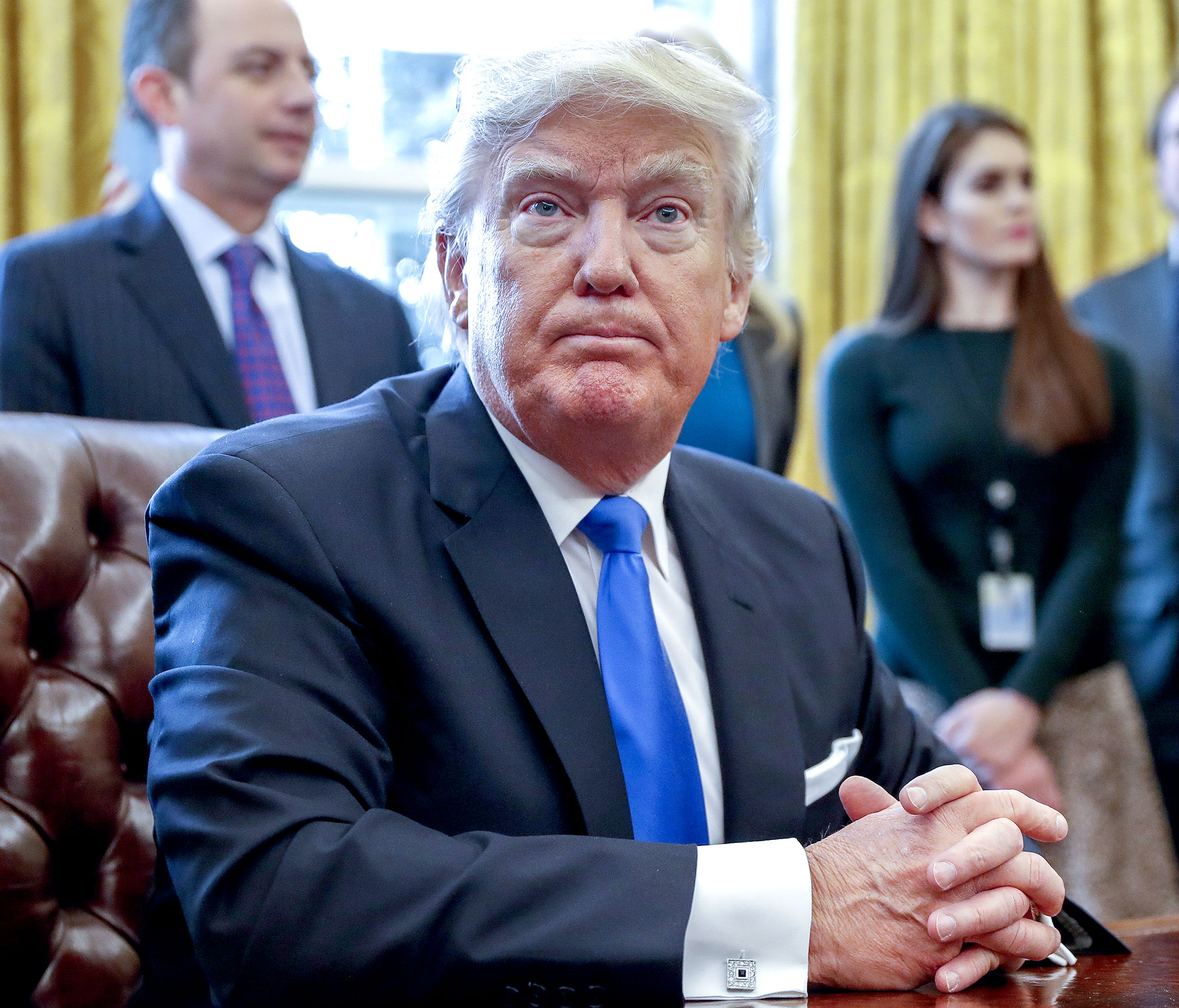 Donald Trump sits after signing one of five executive orders related to the oil pipeline industry in the Oval Office of the White House in Washington, D.C., U.S., Tuesday, Jan. 24, 2017.